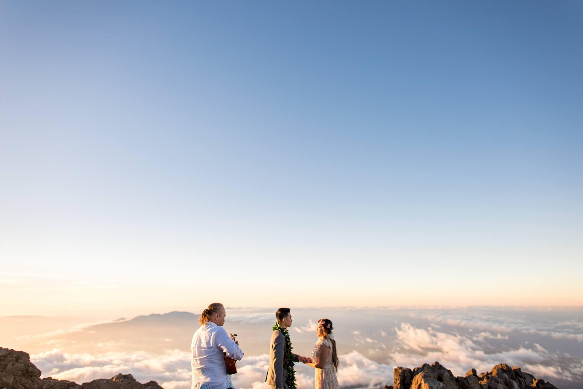 on top of Haleakala, bride groom and minister mid-wedding