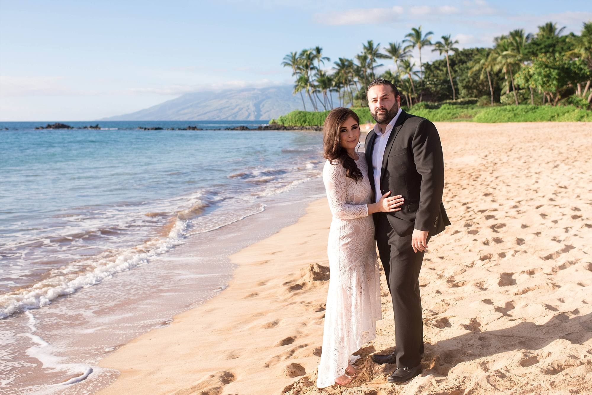 Couple in wedding attire standing on Maui beach