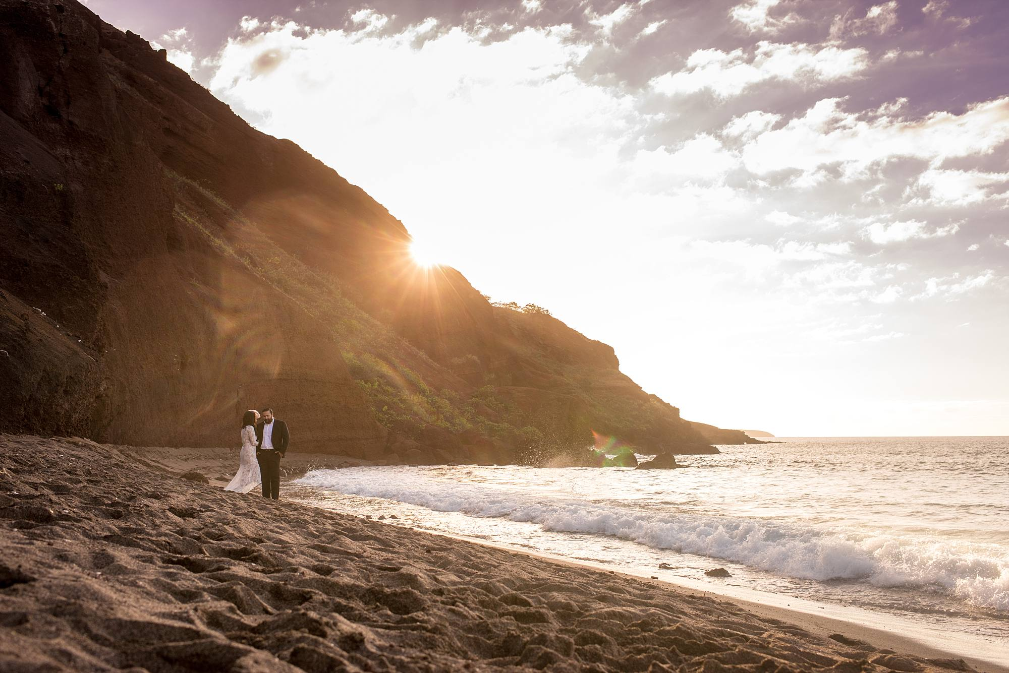 Bride and groom on beach with mountain in background light cascading over it