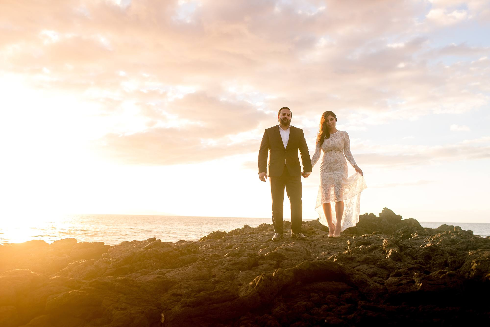 wedding couple standing atop lava rocks