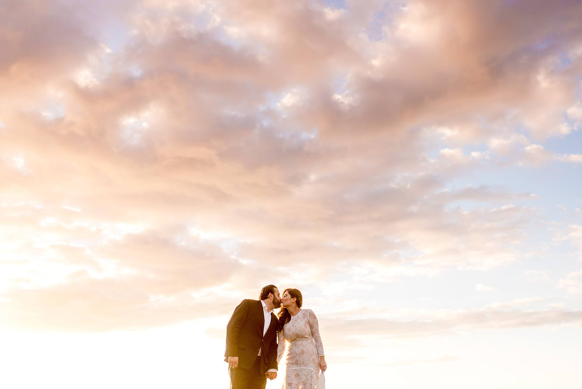newlyweds kissing with clouds above them