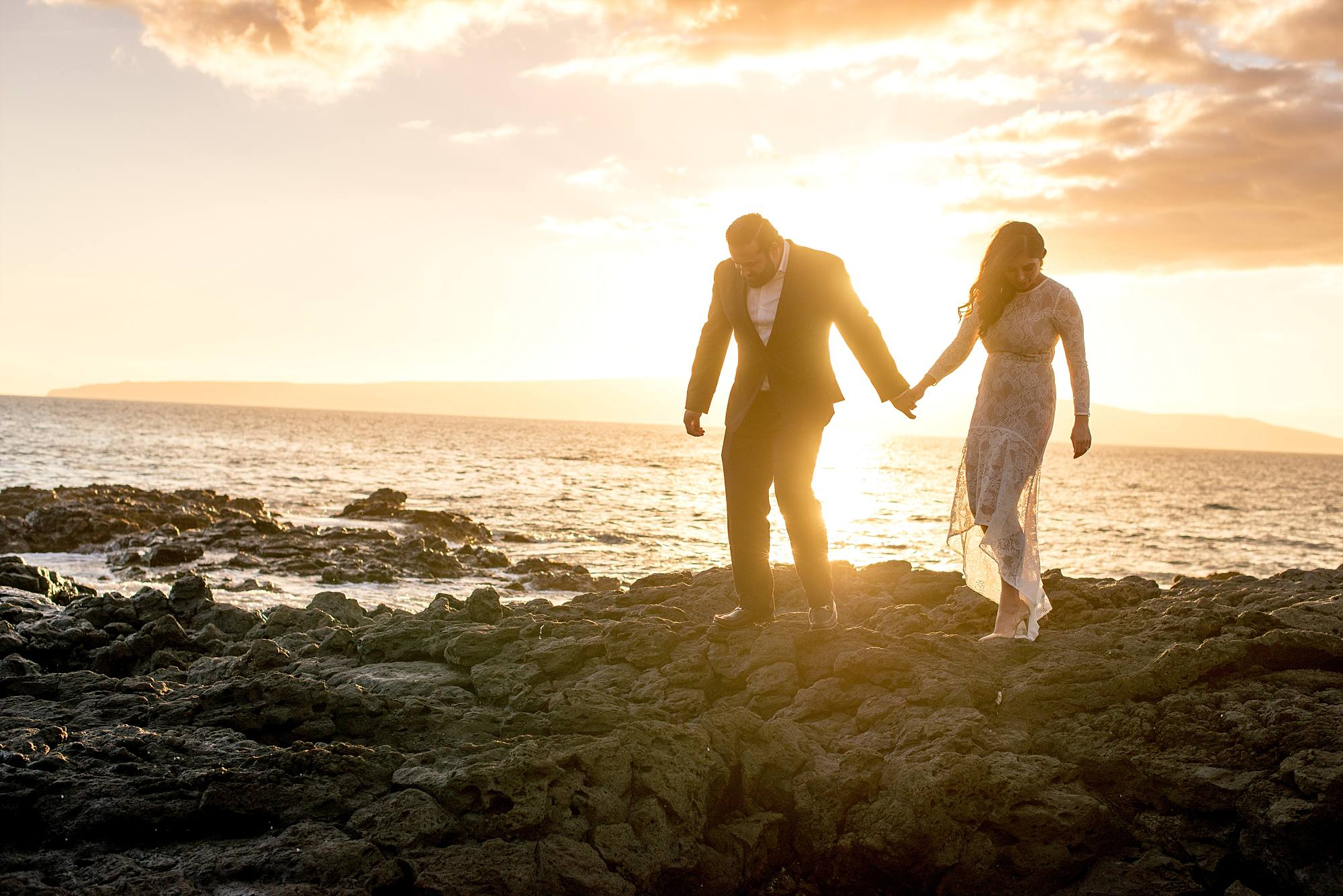 man and woman traversing lava rocks in their wedding attire