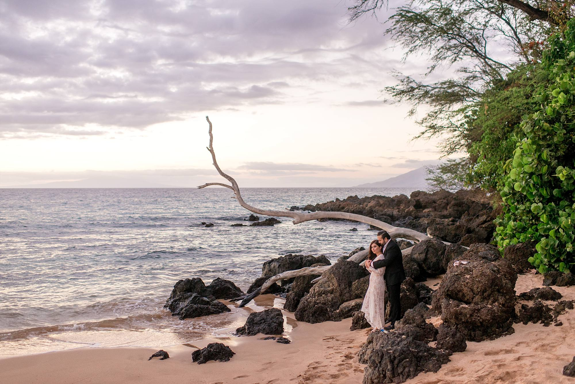 newlywed shot standing on beach hugging with lava rock and ocean in the background