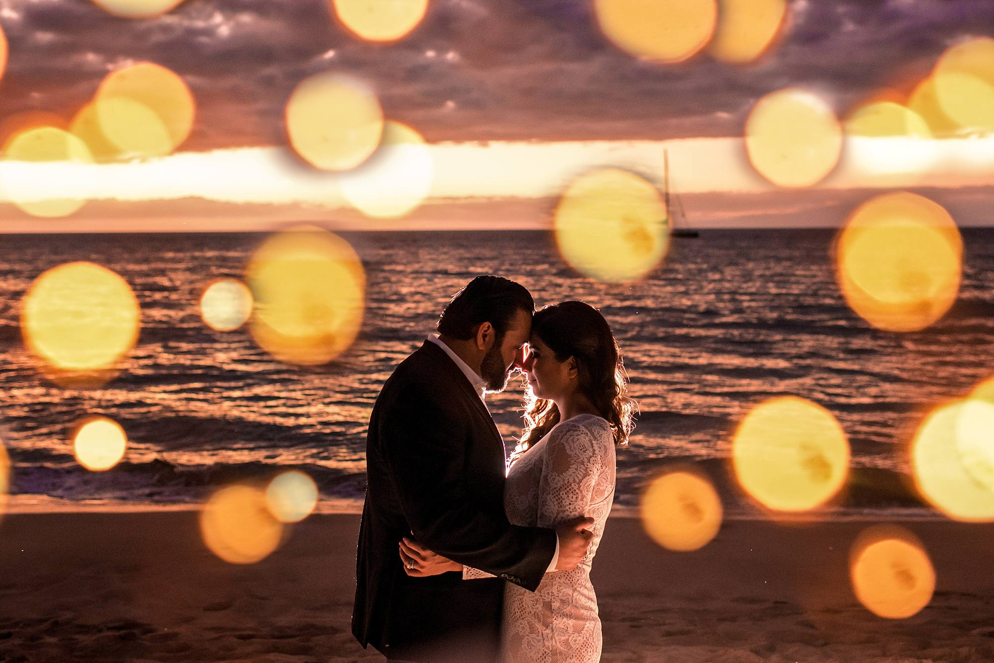 newlyweds embracing with light globes around them