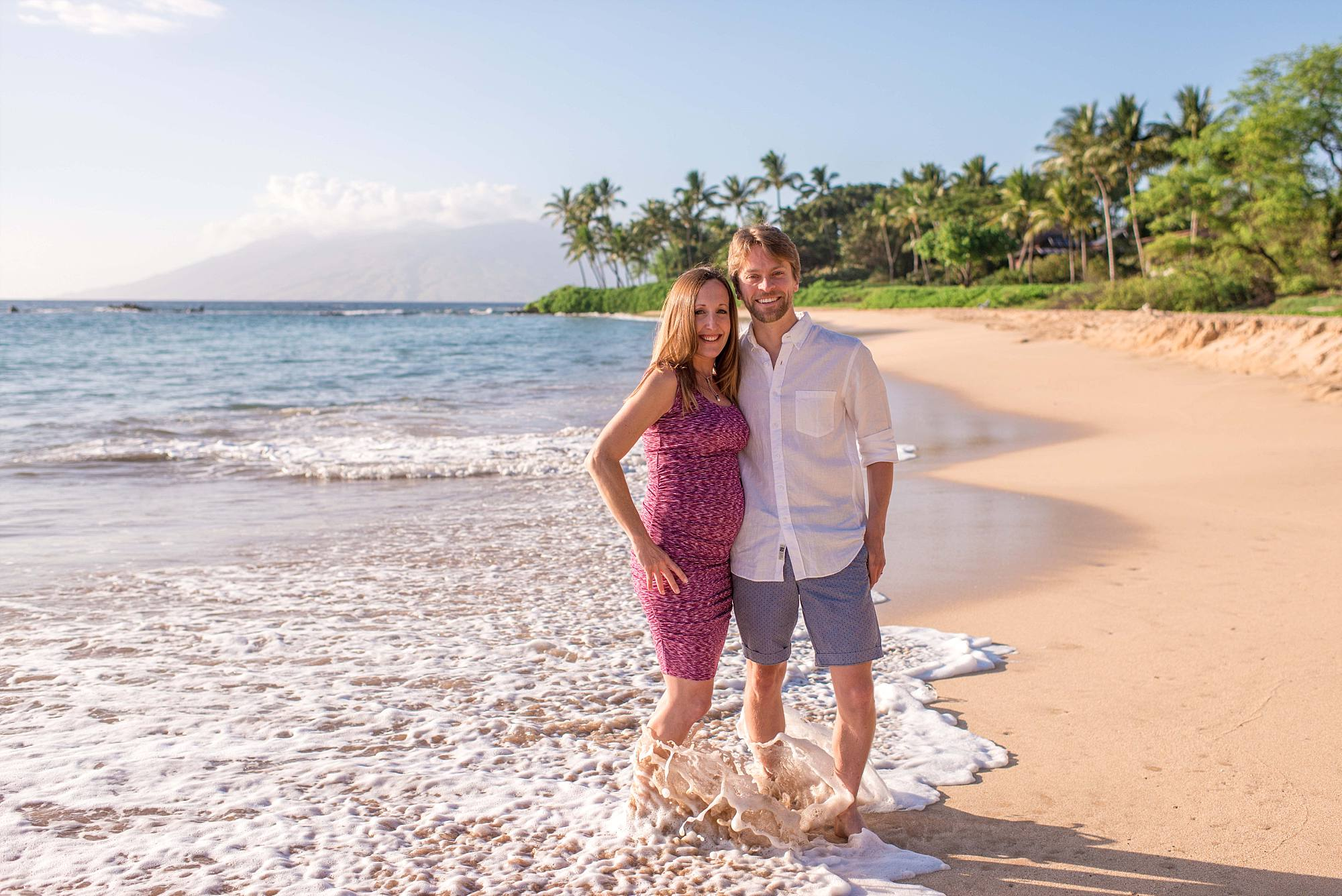 pregnant woman with her husband. feet in the Maui surf