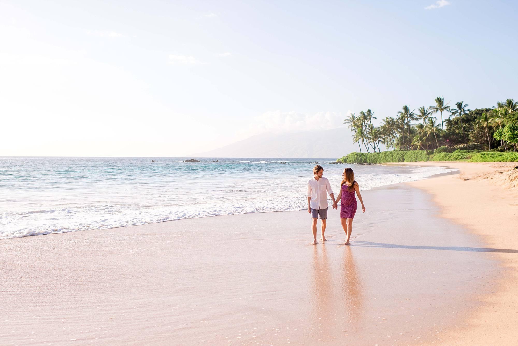 baby moon couple walking down Maui's white sand beach