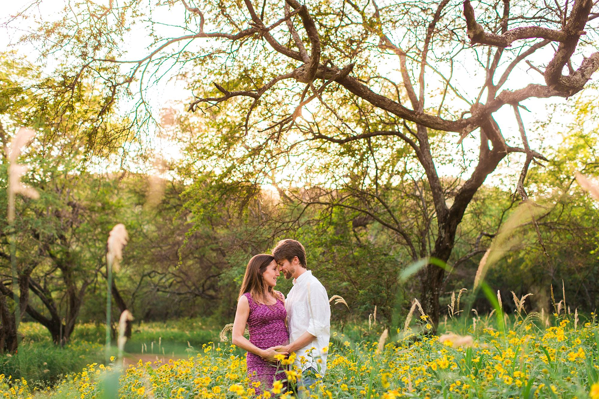 couple standing head to head in yellow flowers with knotty trees behind them, cradling pregnant stomach