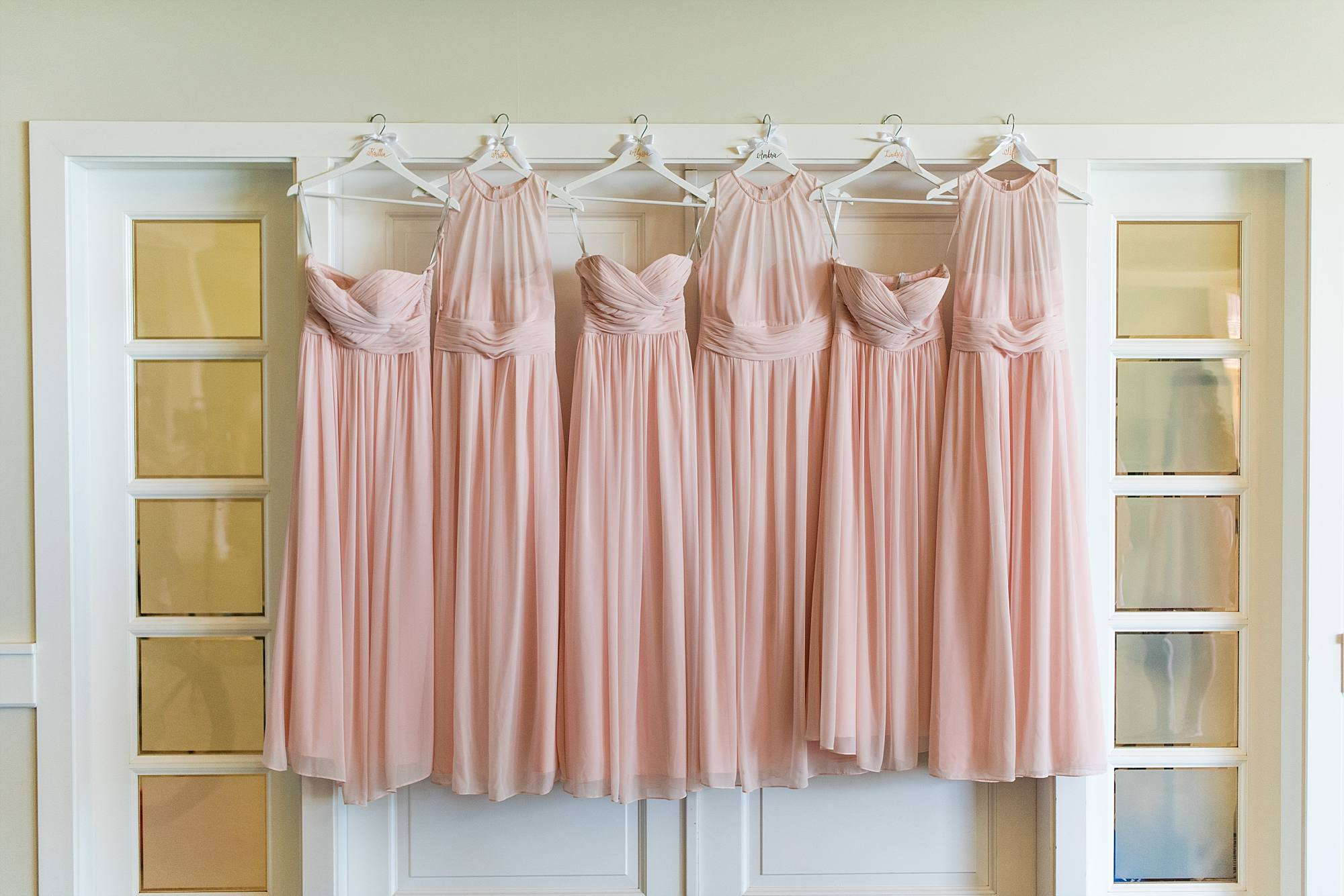 light pink bridesmaids' dresses hanging all together