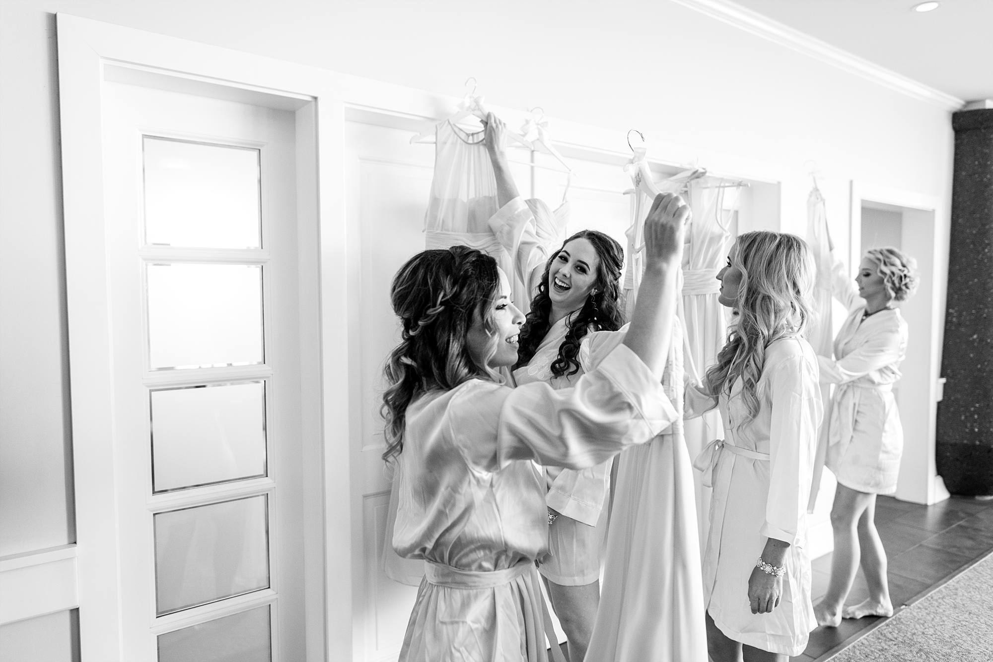 bridesmaids looking at their dresses as they're getting ready