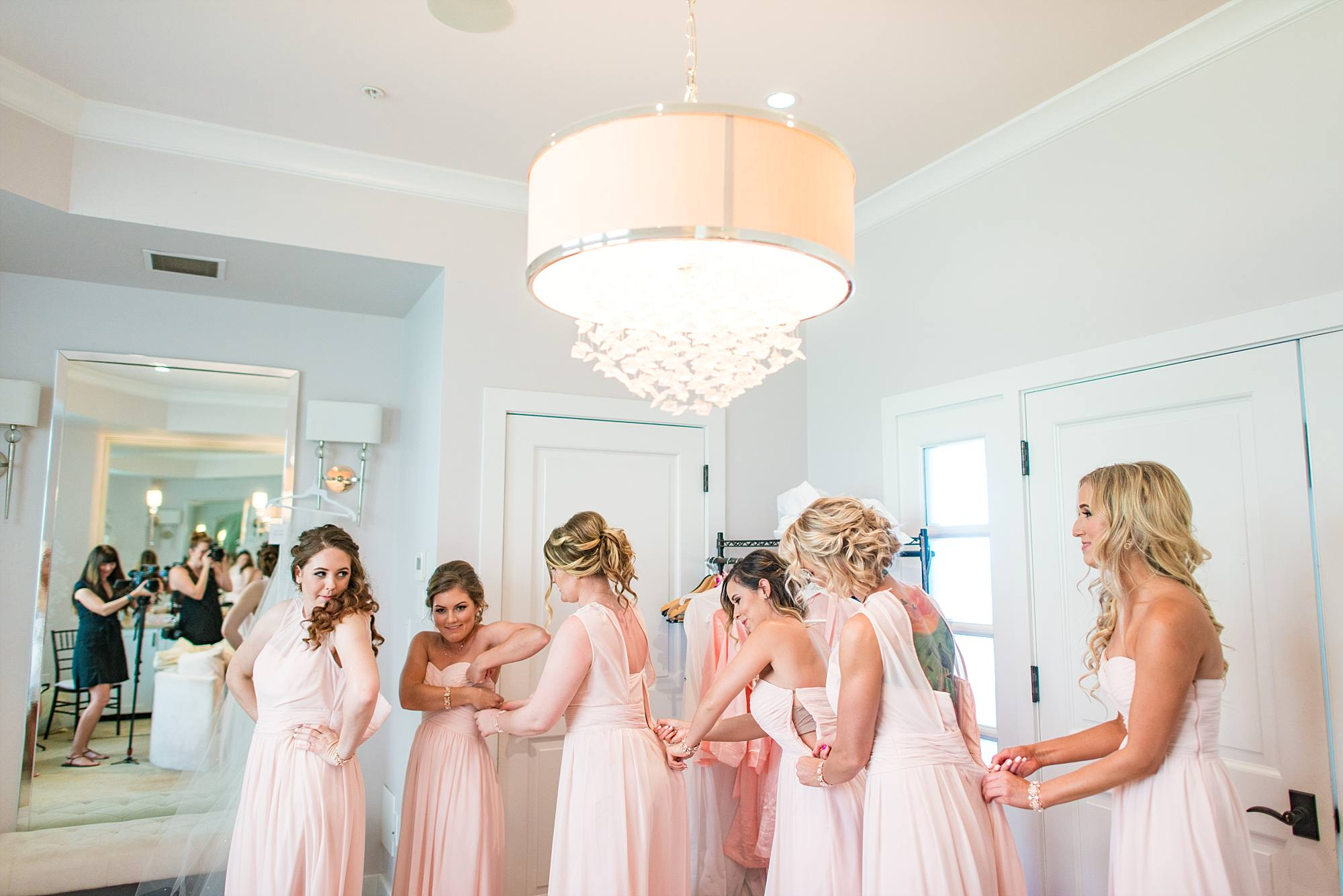 bridal party all helping each other zip up each others pink bridesmaid dresses