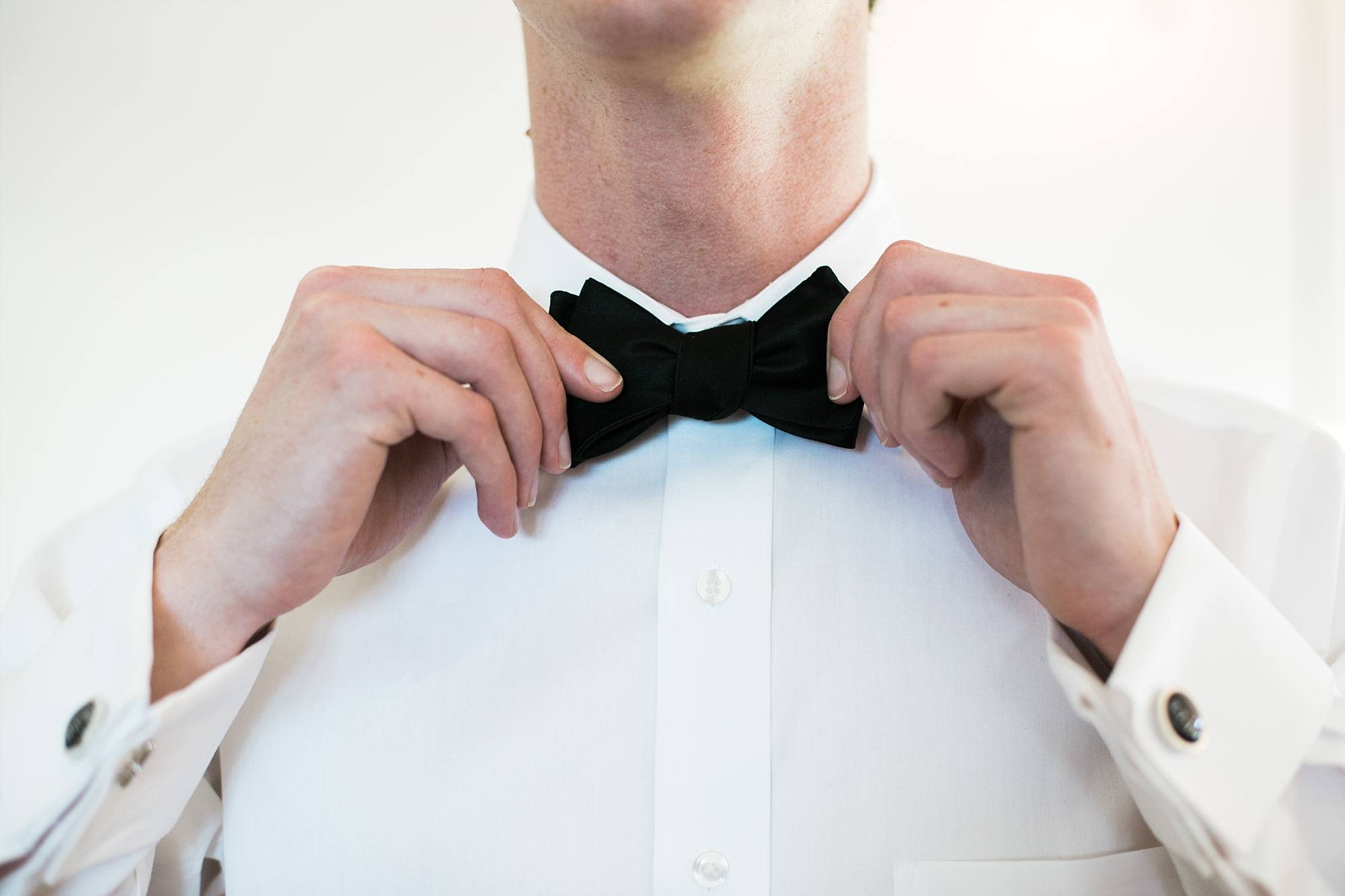 groom putting on his black bow tie