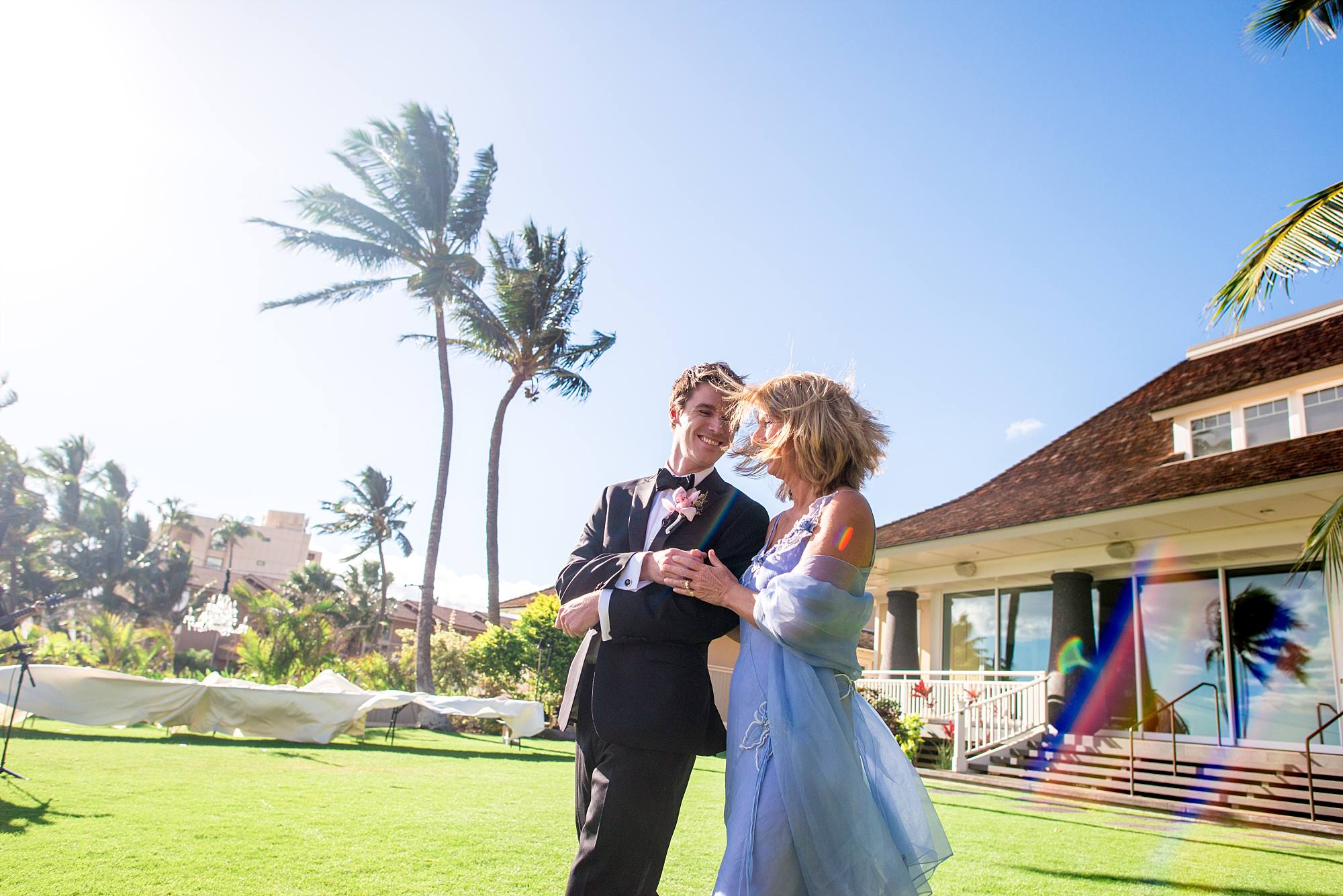 Groom walking his mother down to her seat with palm trees swaying in background
