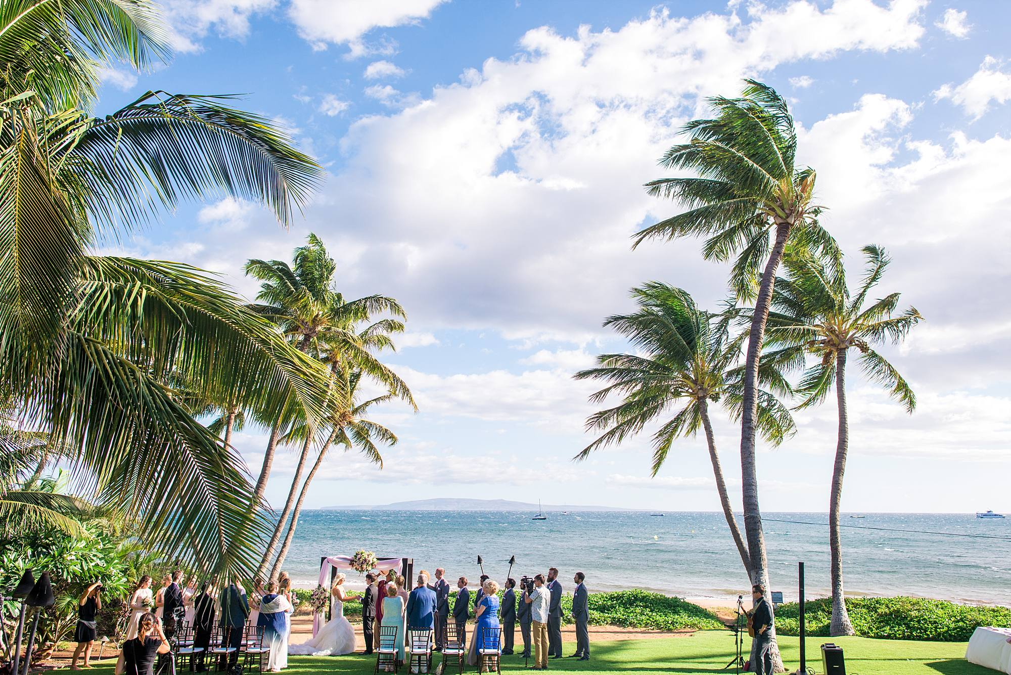 Maui Wedding at the sea shore, all the guests are standing at their chairs as the bride has just come down the aisle. Sun, sea, and palm trees.