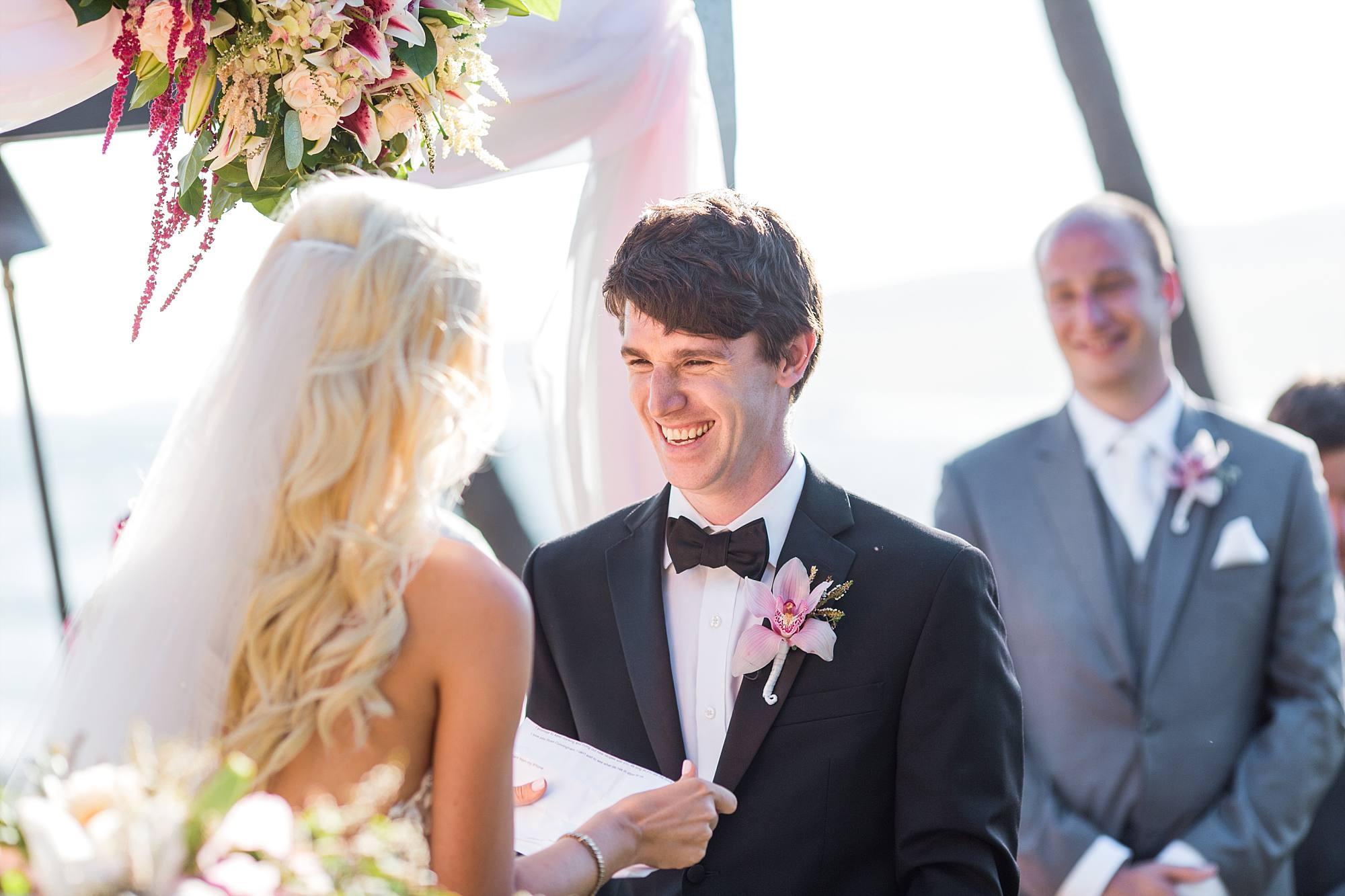 groom laughing as his bride reads her self-written vows