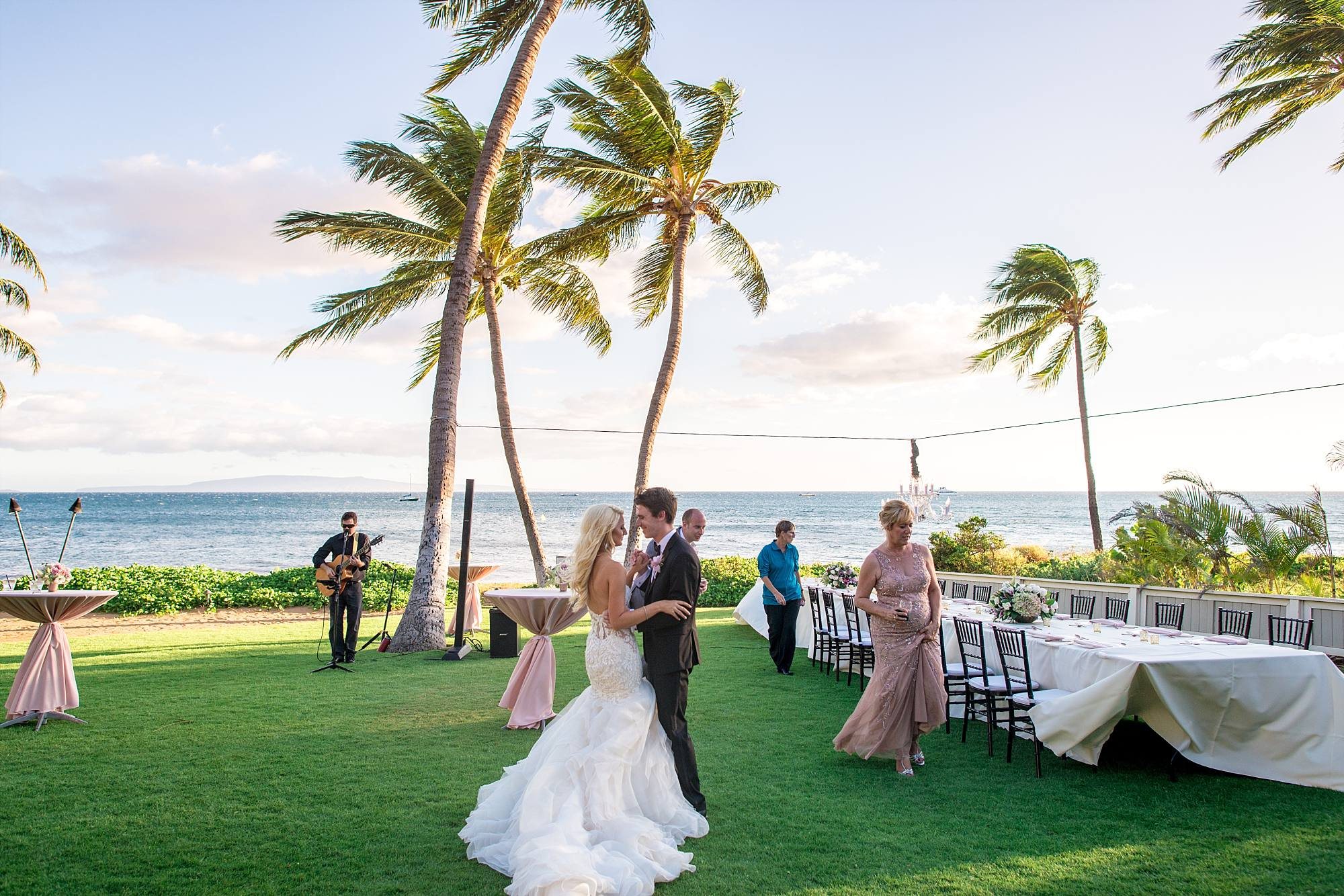 bride and groom dancing their first dance at their tropical wedding with palm trees swaying in the wind behind them