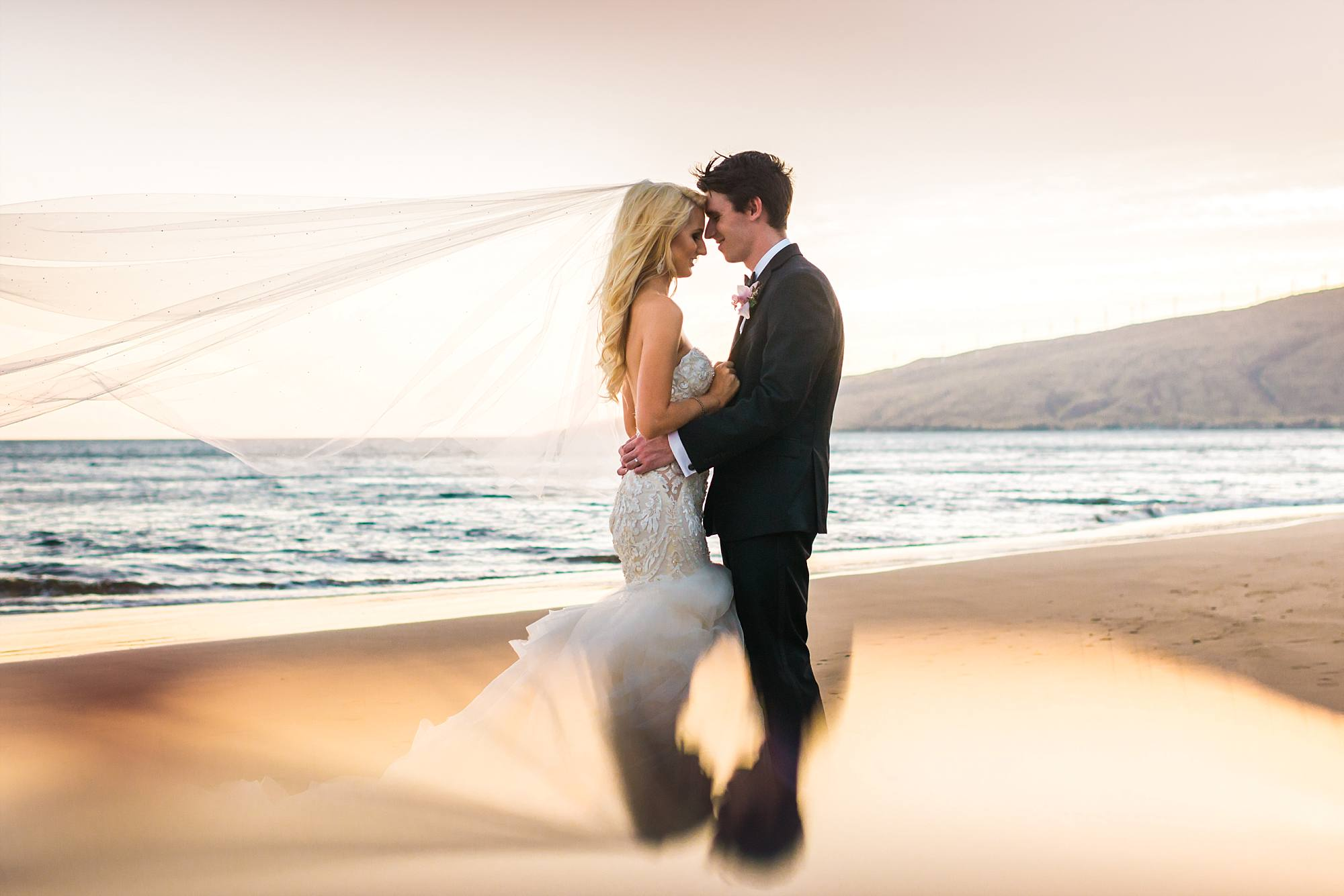 bridal couple shot with incredible reflection and veil sweeping out over the sand