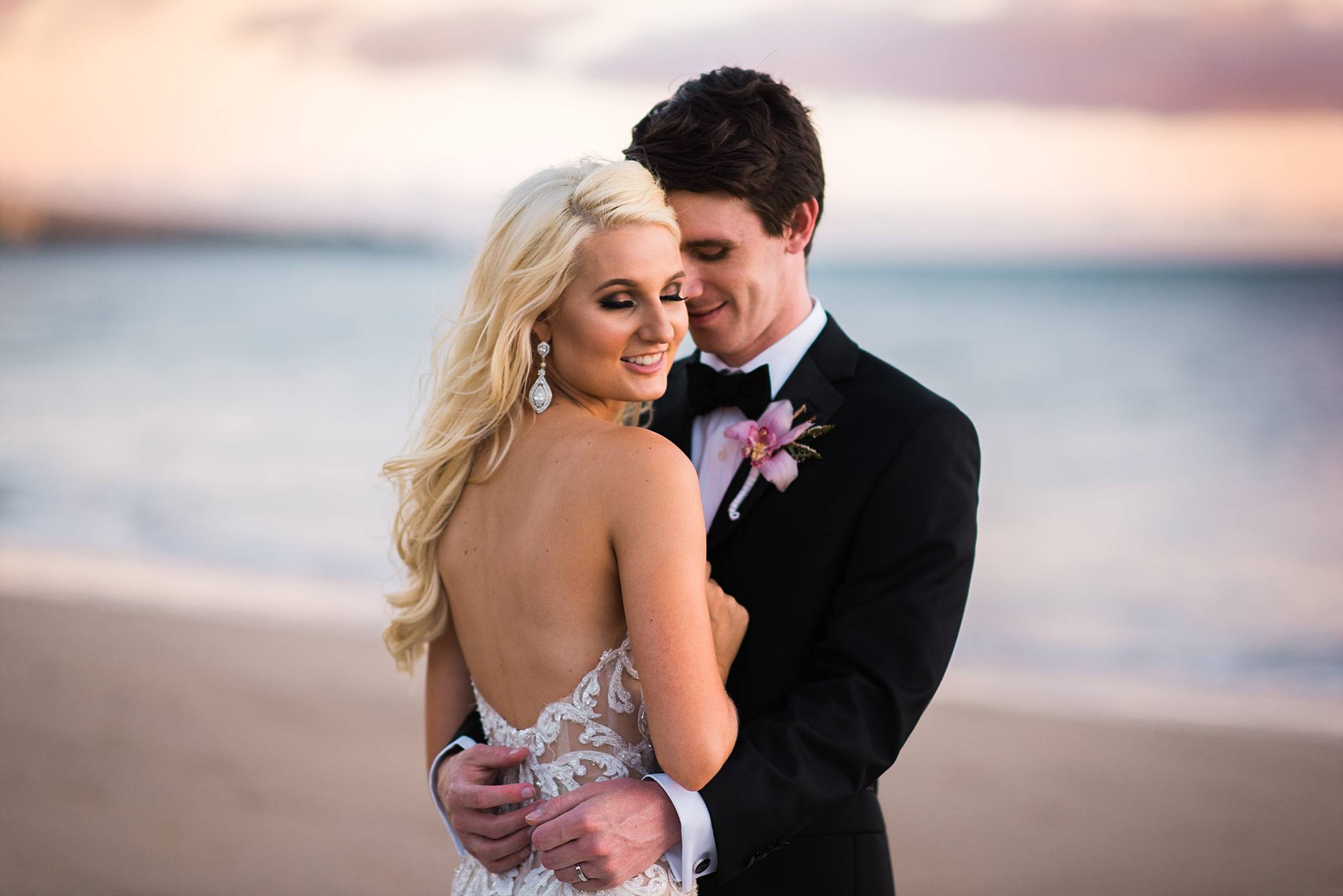 sweet bridal shot with wind in her hair, couple hugging, sand and water behind them