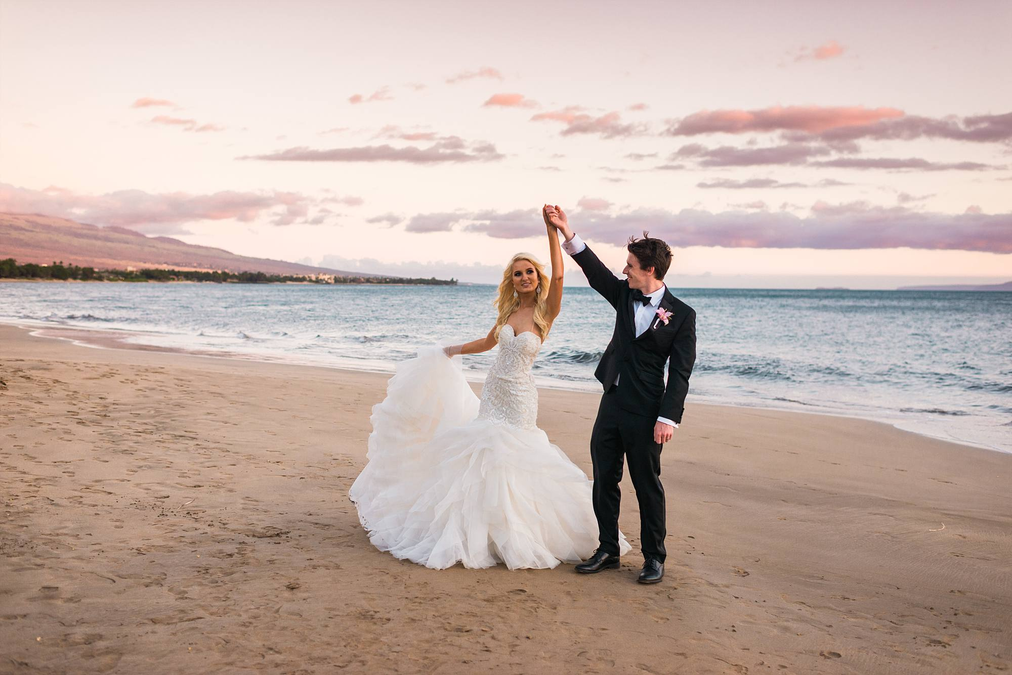 husband twirling his new wife on beach at sunset, pink clouds in sky
