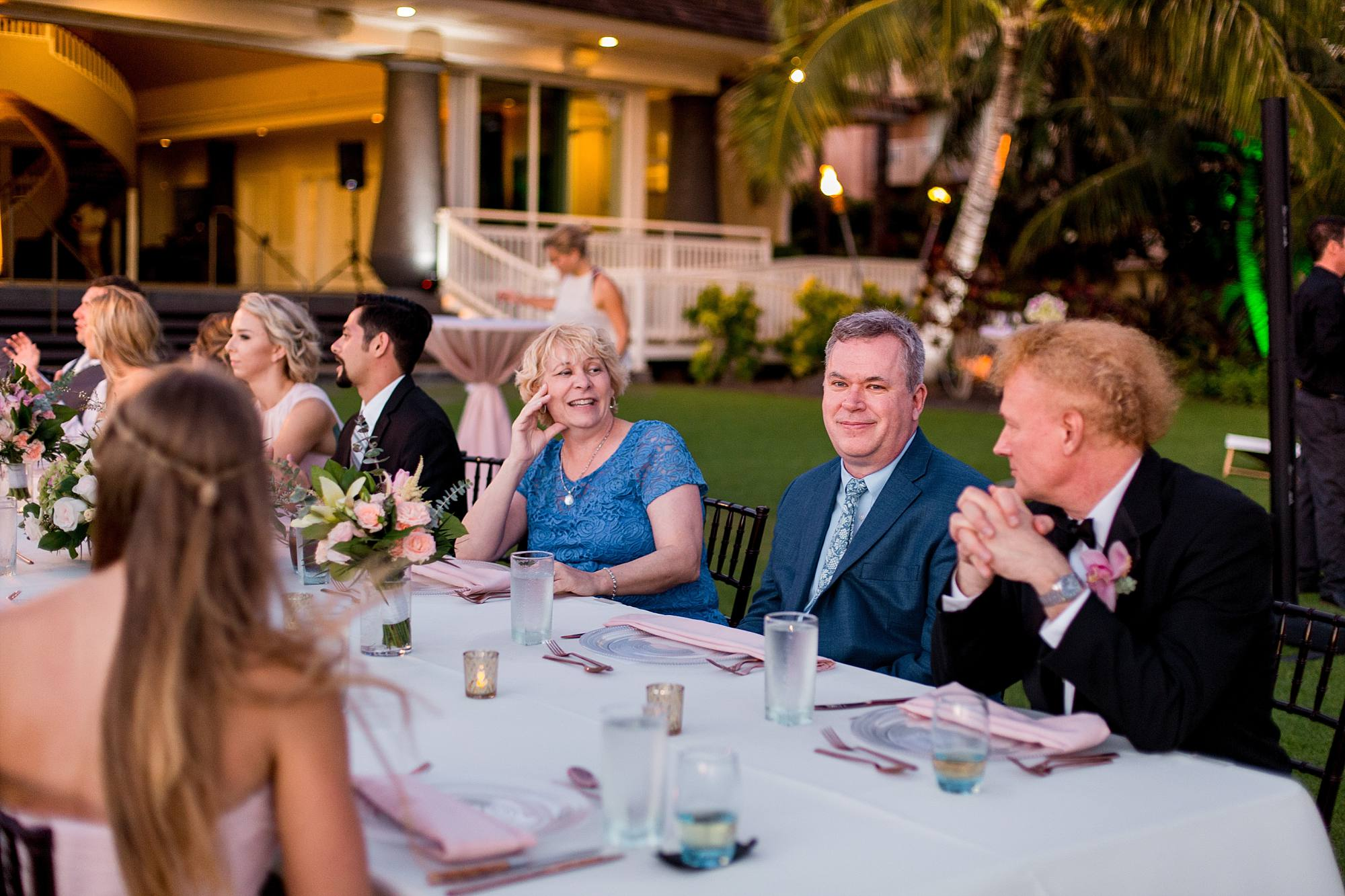 family sitting at farm table for wedding
