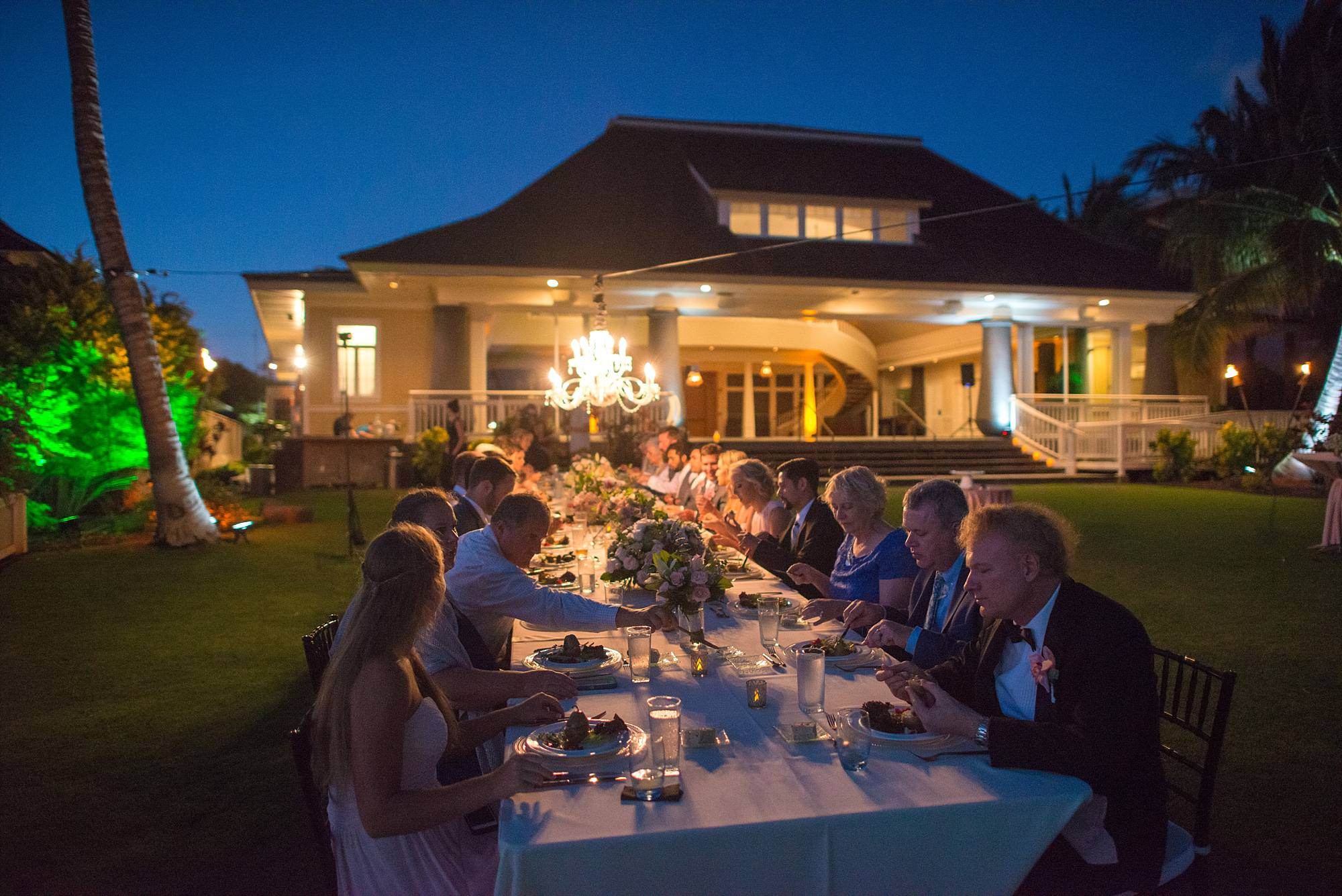 all wedding guests sitting together at beautiful farm table eating and drinking during reception, Sugar Beach Events house in distance