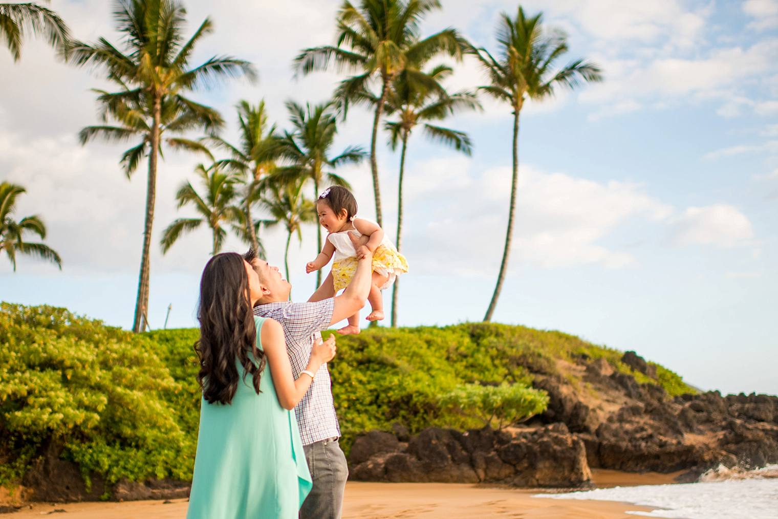 family playing with their daughter on the beach in maui