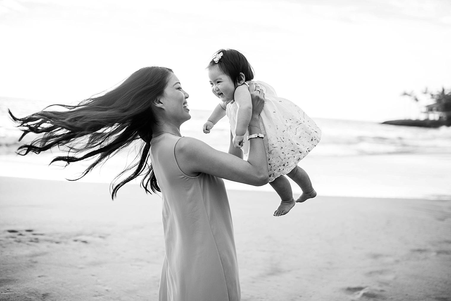 mother playing with daughter on beach in maui