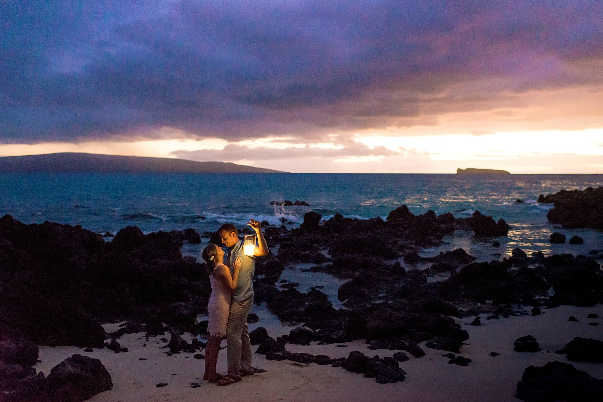 afterdark shot with couples on the beach with a lantern