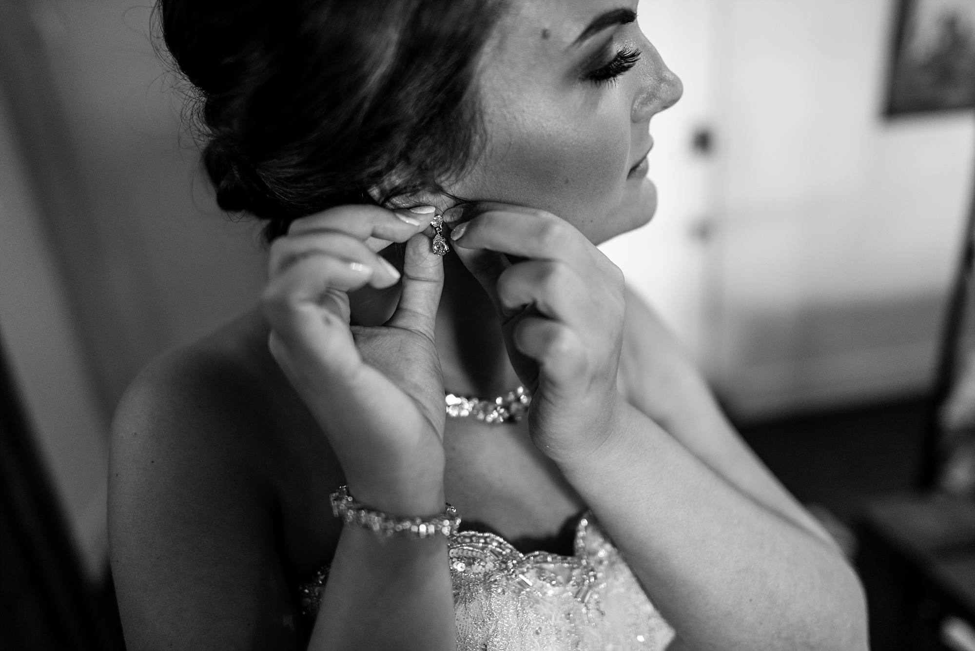 black and white image of bride putting on earrings