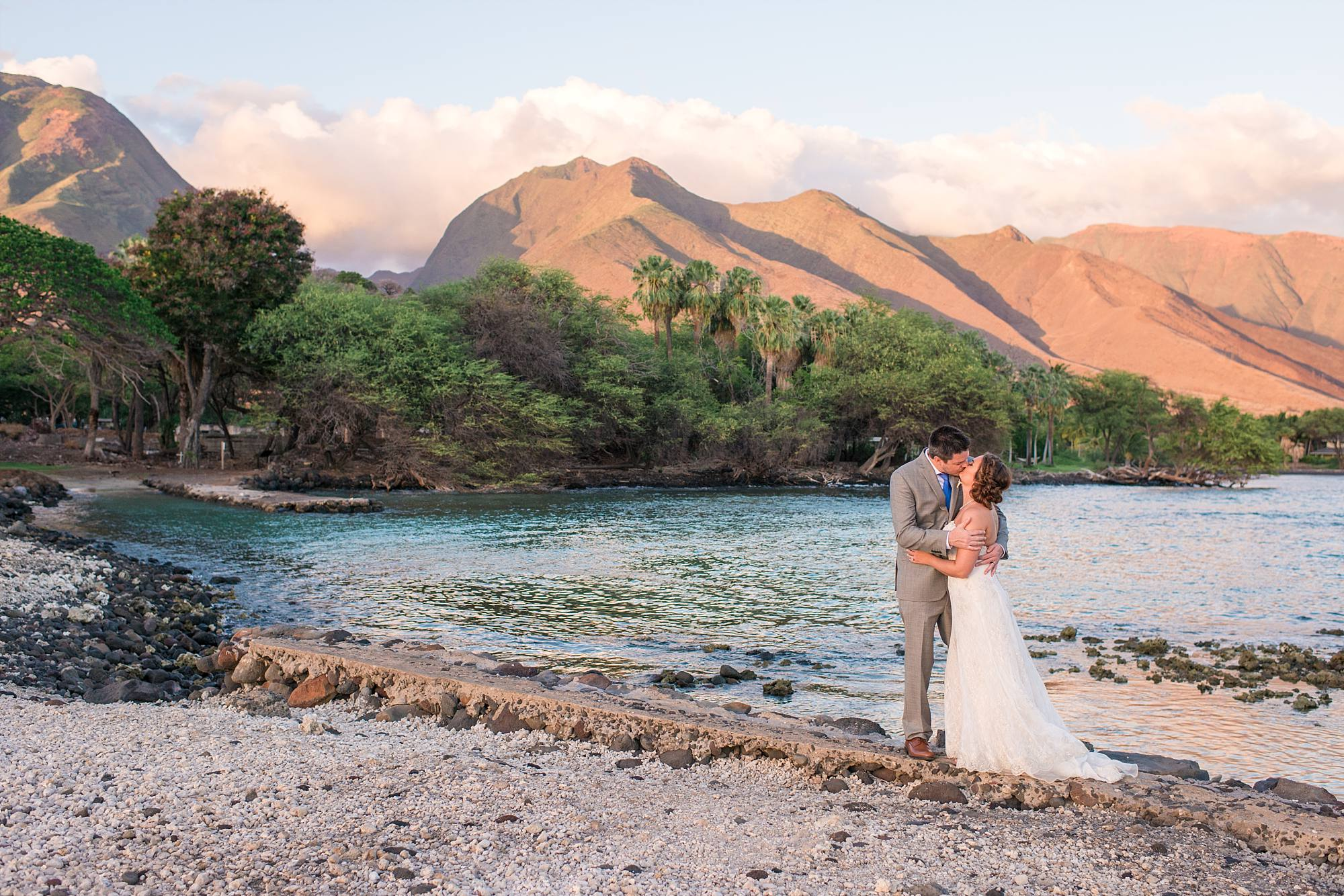 just married couple kissing with West Maui Mountains in the background