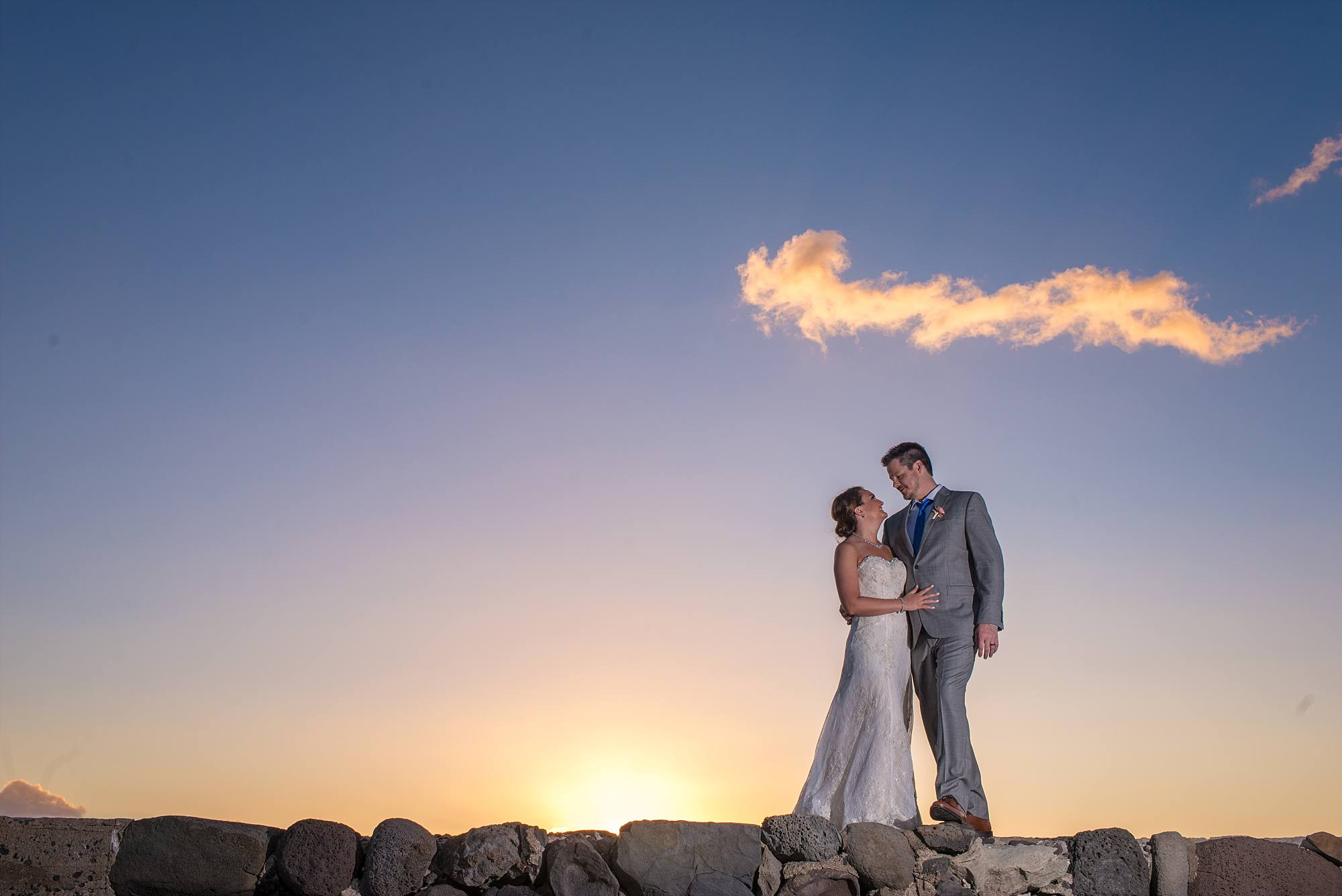 bride and groom on top of rocks