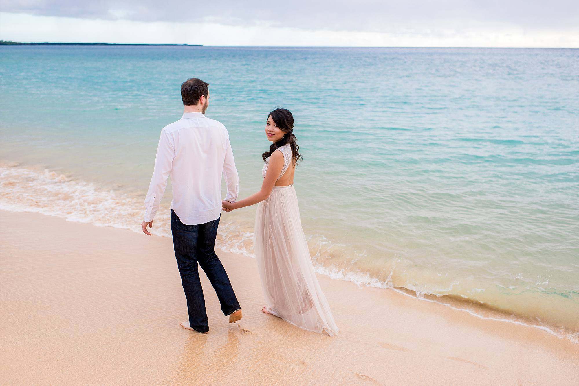 blue ocean and newly engaged couple walking hand in hand on the sand away from camera