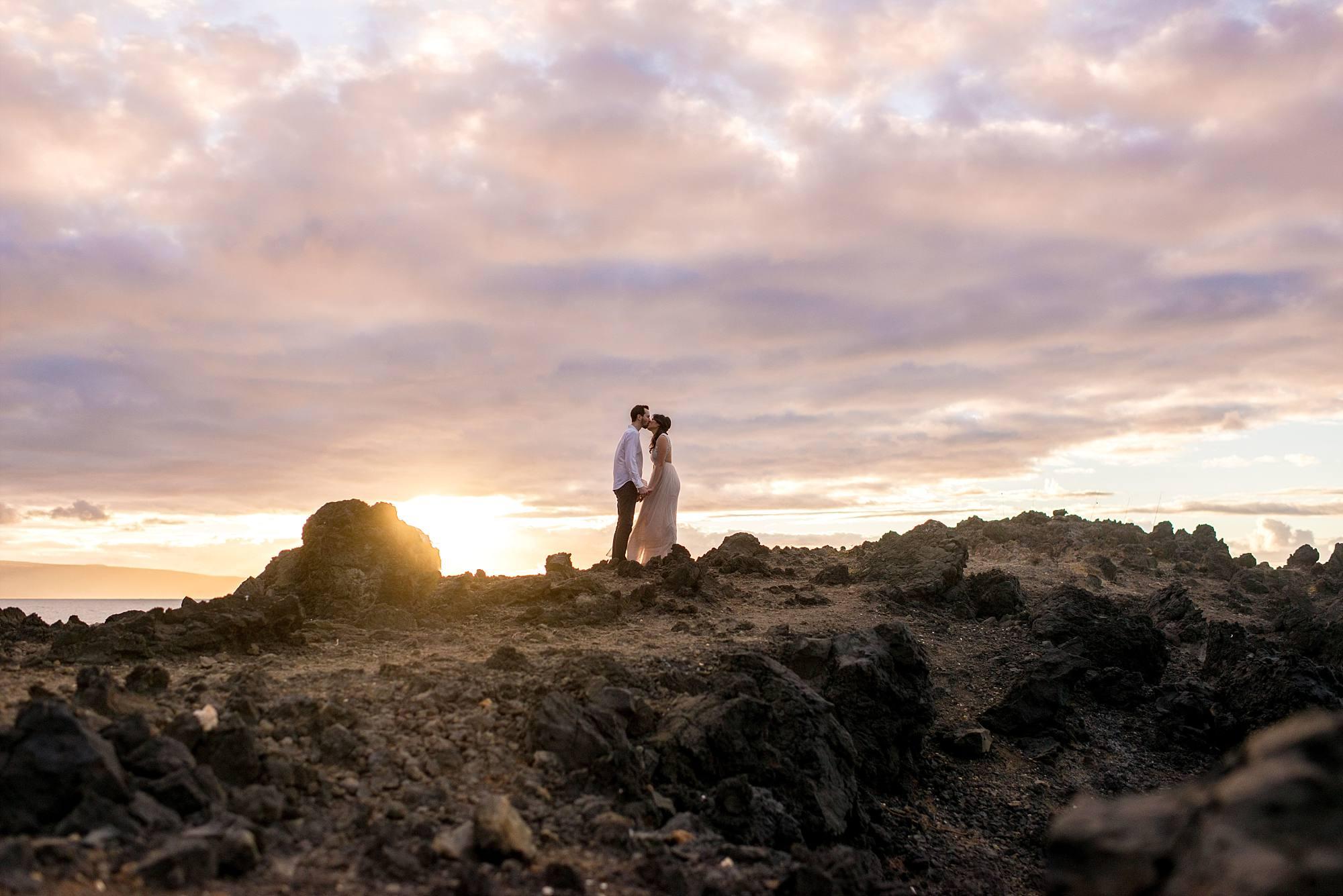 fiances kissing atop lava rock