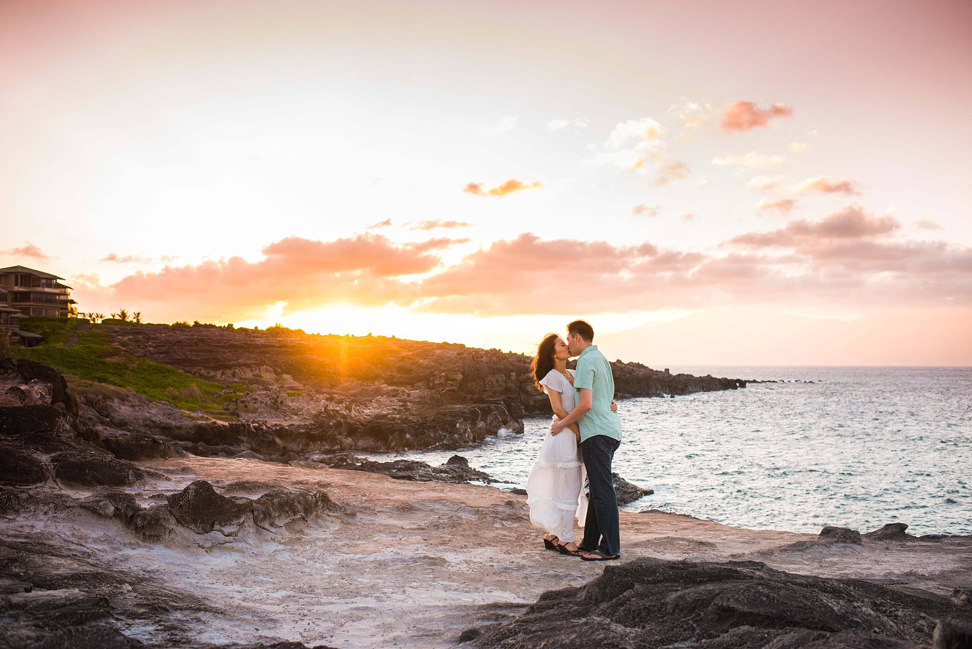 amazing sunset hitting the rocks, couple kissing on cliff