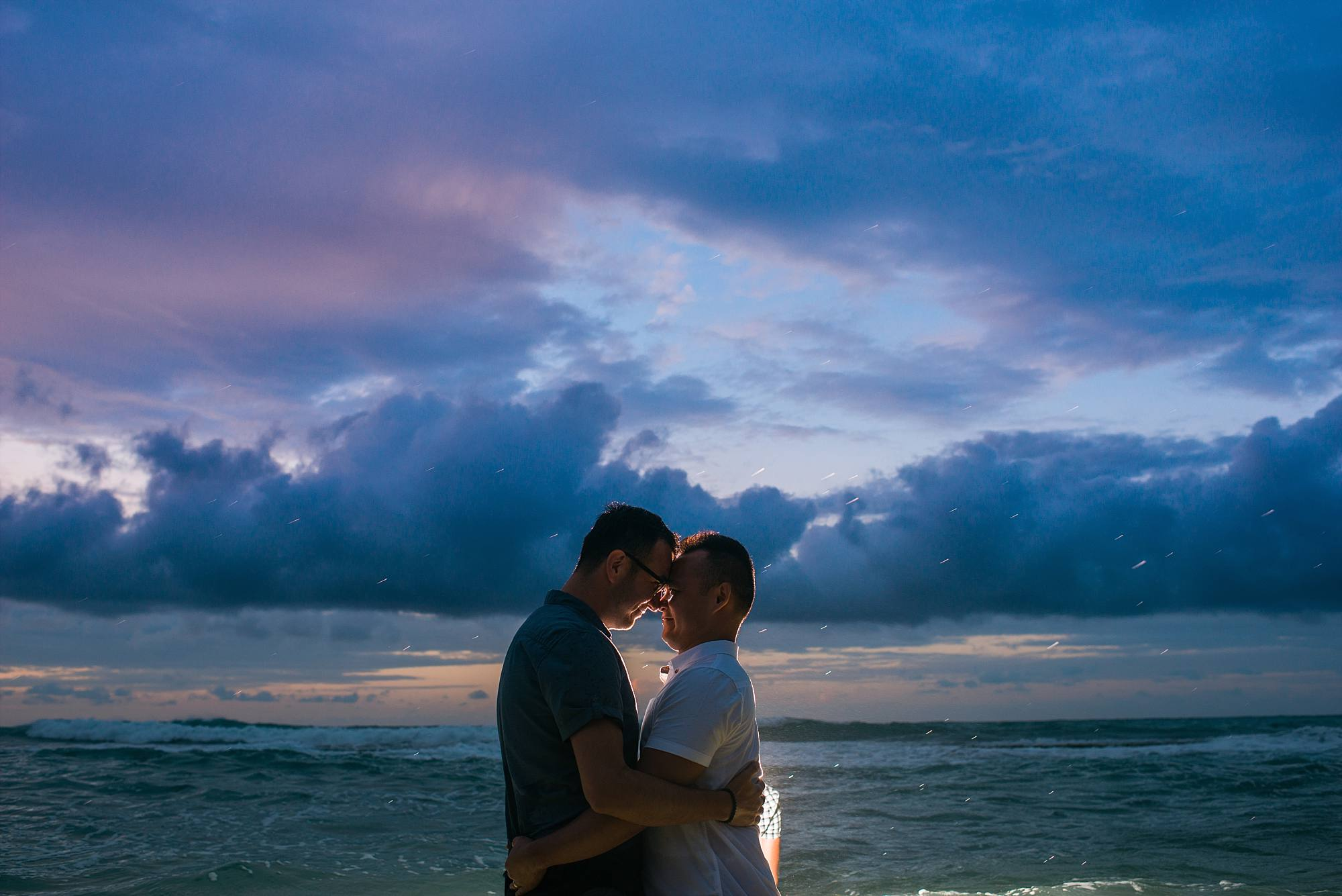 sunset , backlit shot Maui engagement photos, couple hugging, incredible clouds and the ocean
