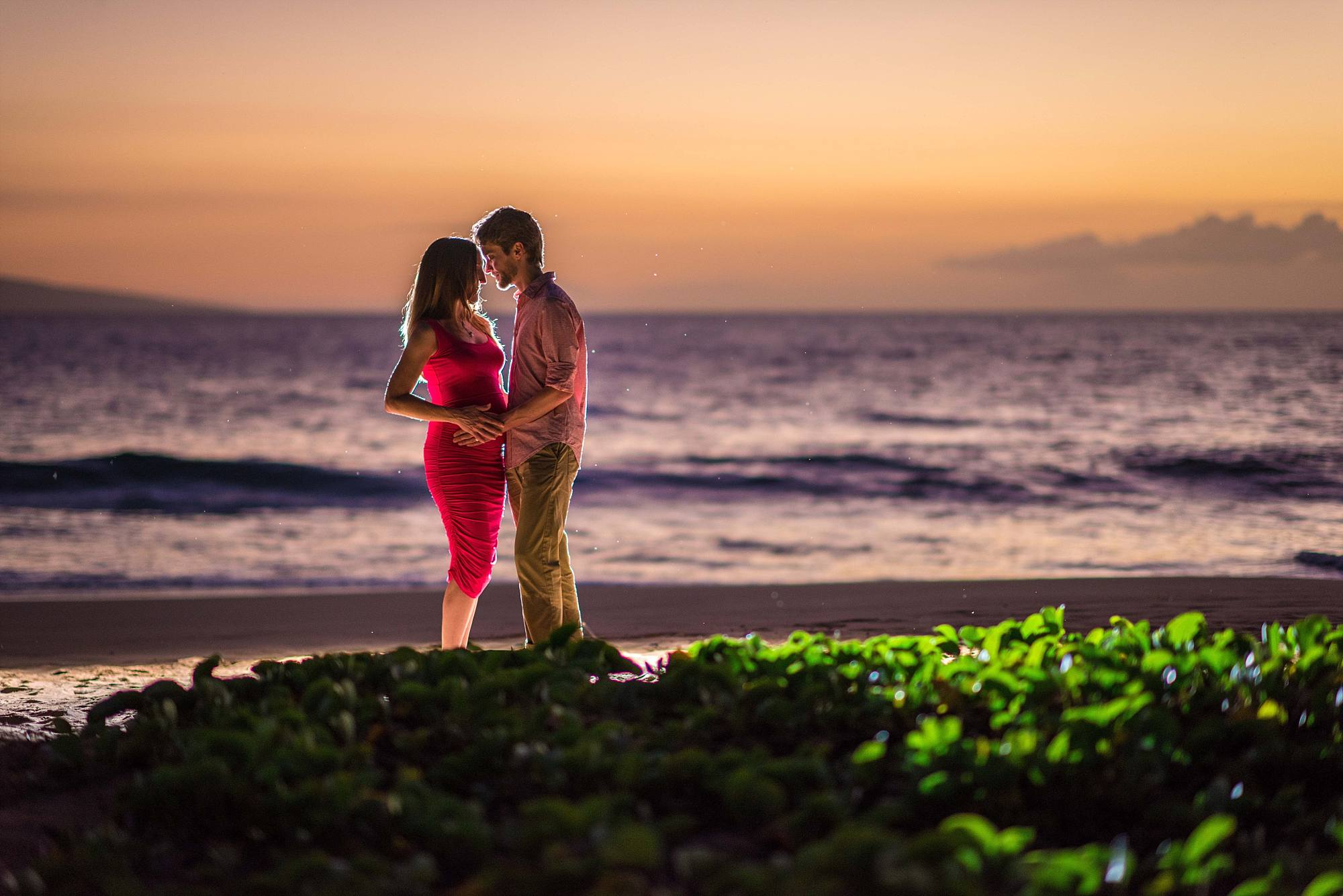 man loves on his pregnant wife during the romantic Maui sunset