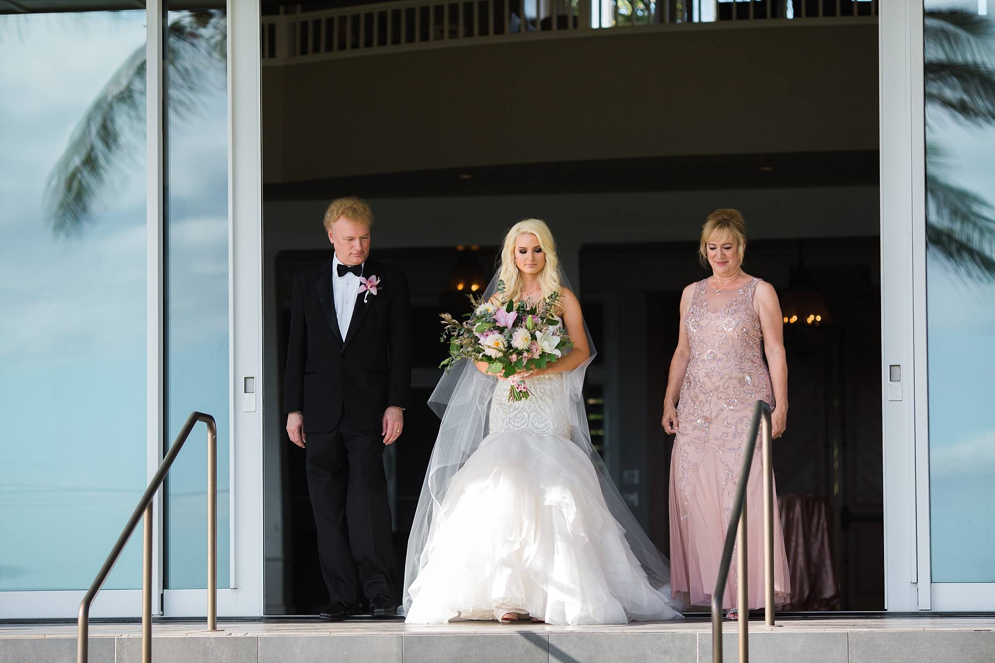Bride and parents walking out to the ceremony, the first time the crowd wees her
