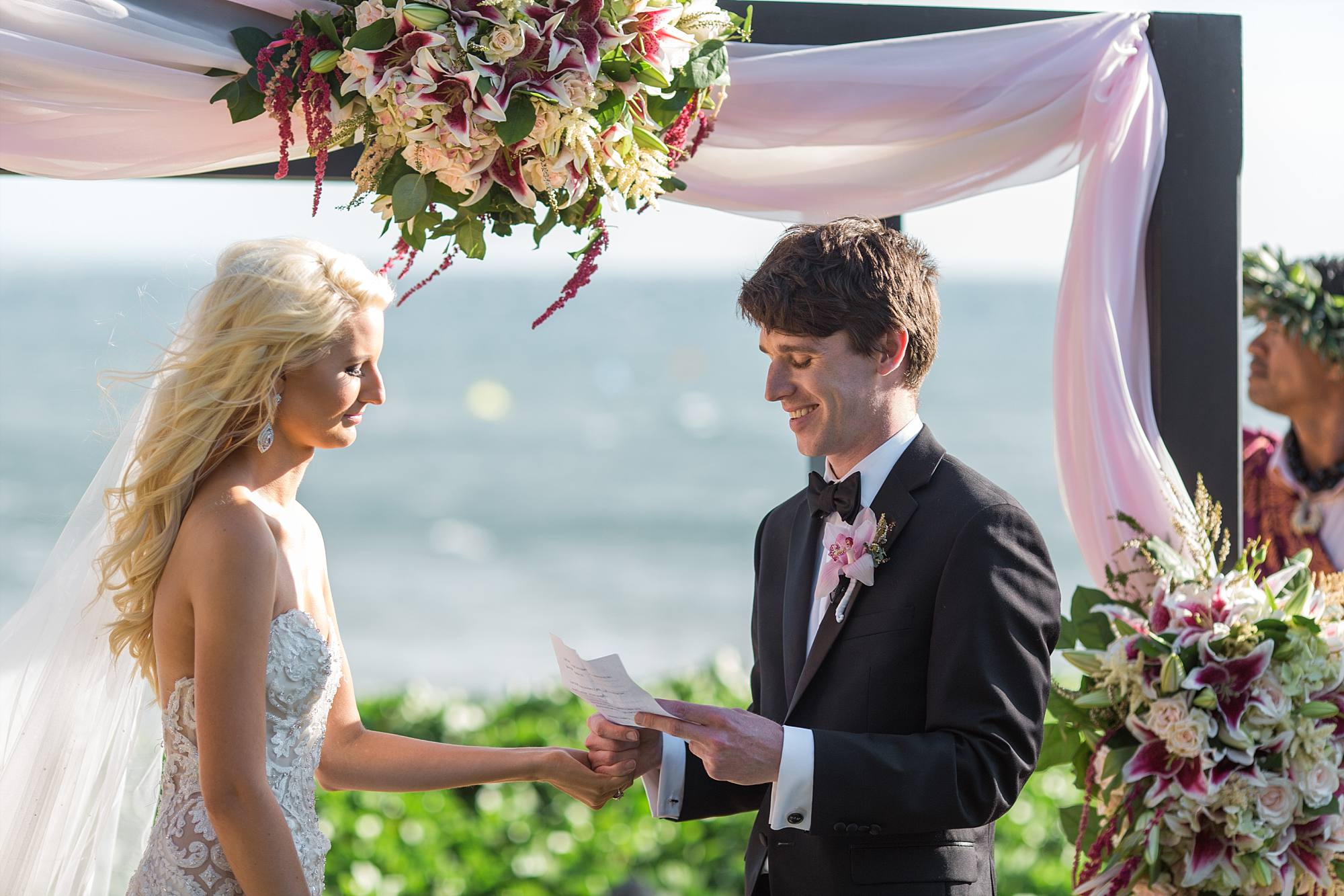 Groom reading his vows that he wrote himself, holding hands with his bride. The Pacific Ocean behind them