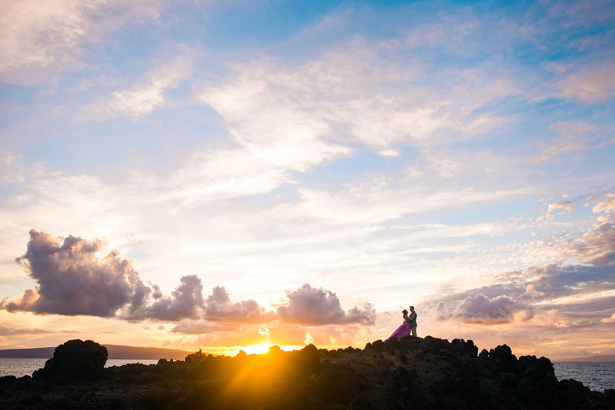 newlyweds on a lava rock face with incredible Maui sunset behind them