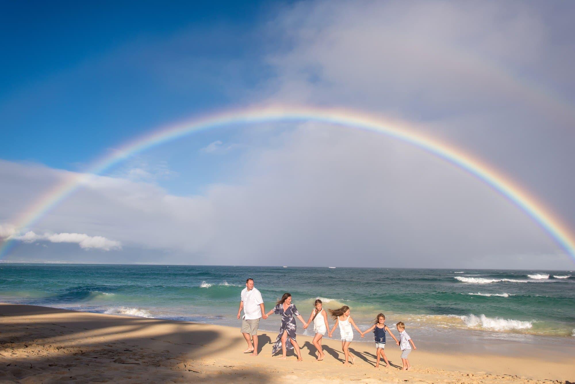 family under a rainbow in maui
