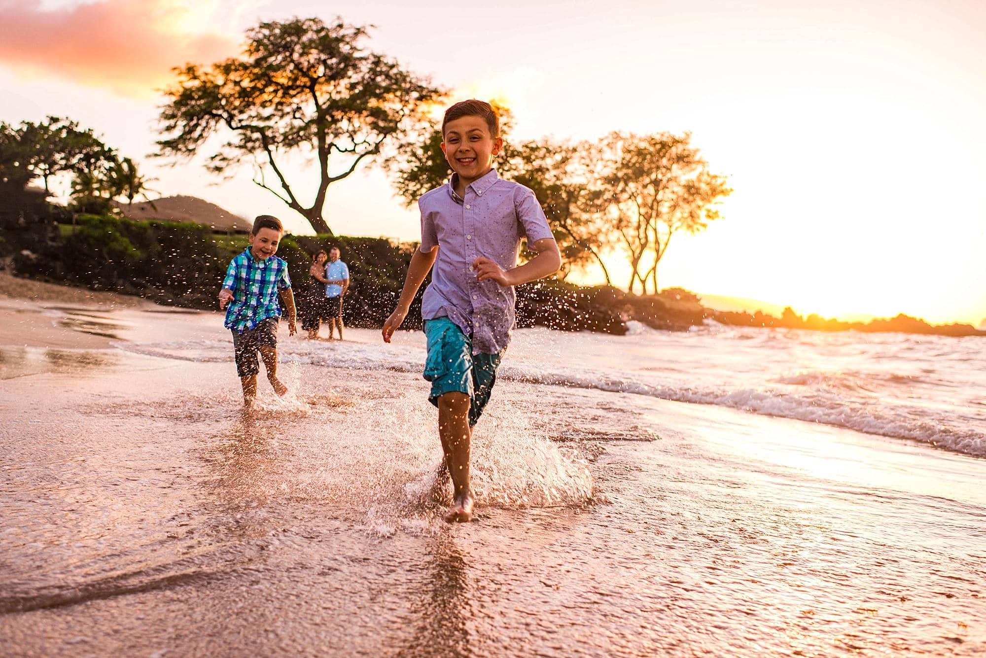 kids running through water at maluaka beach