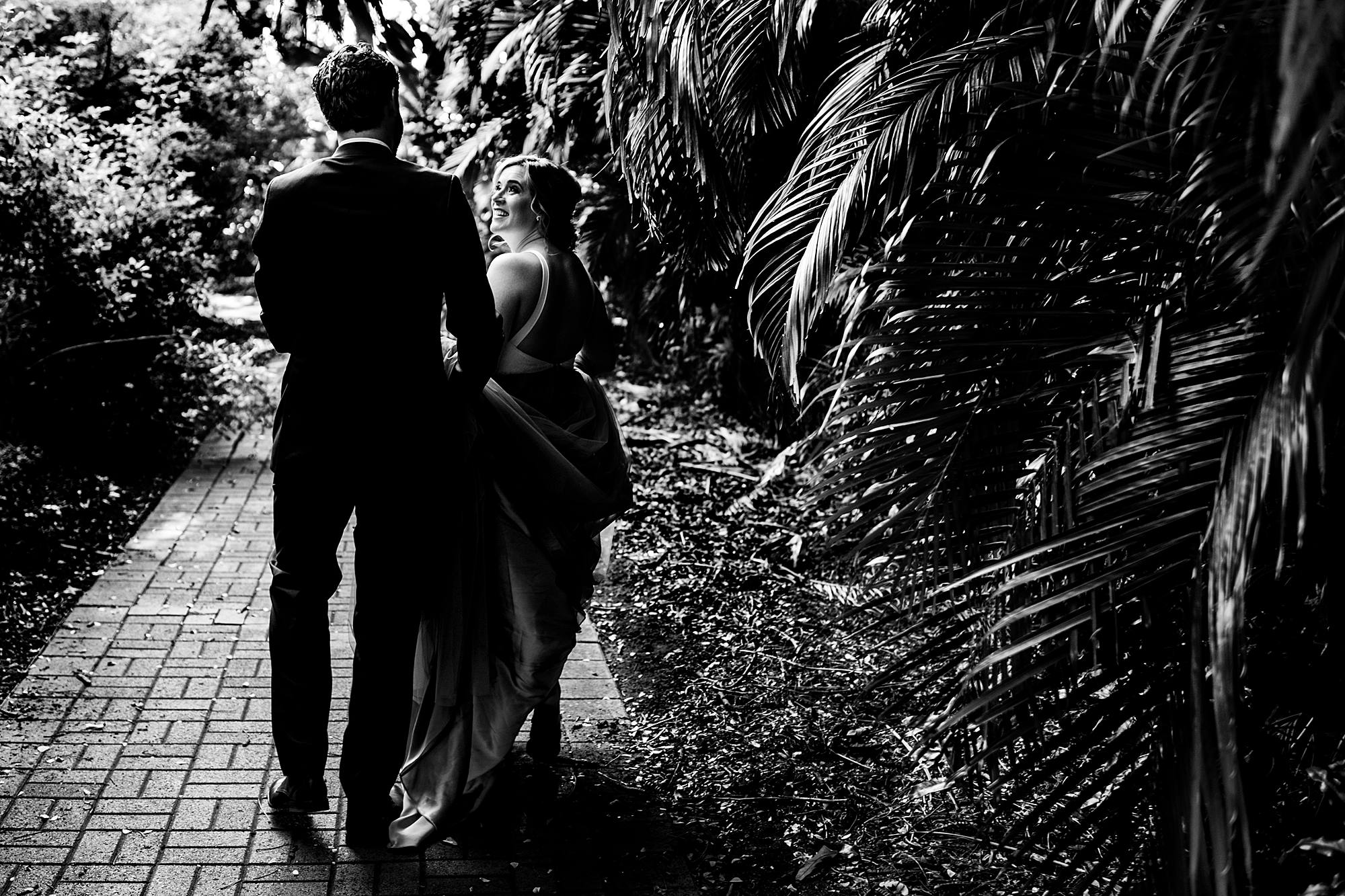 black and white photo of couple walking through the jungle