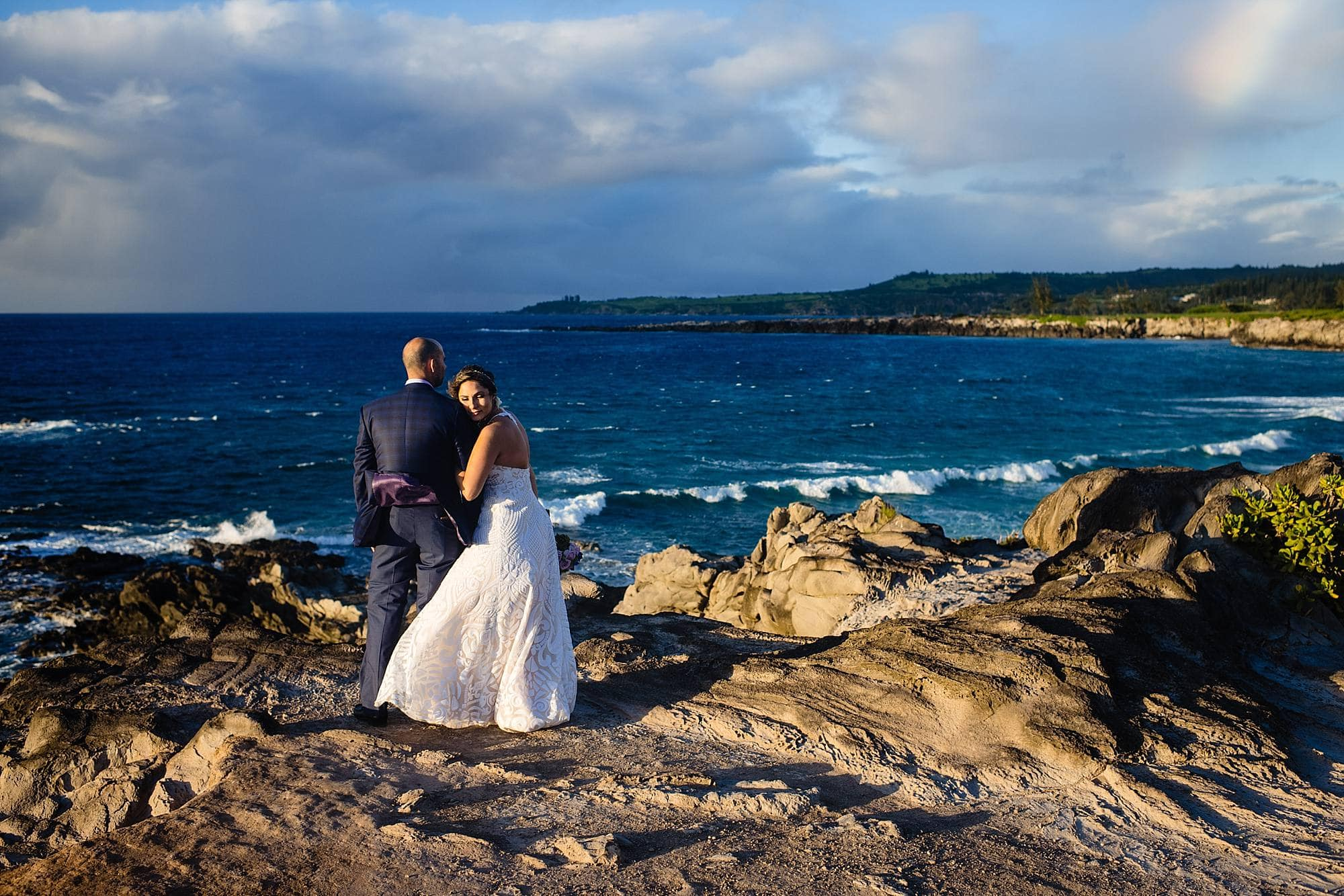 couple on cliff in maui with rainbow