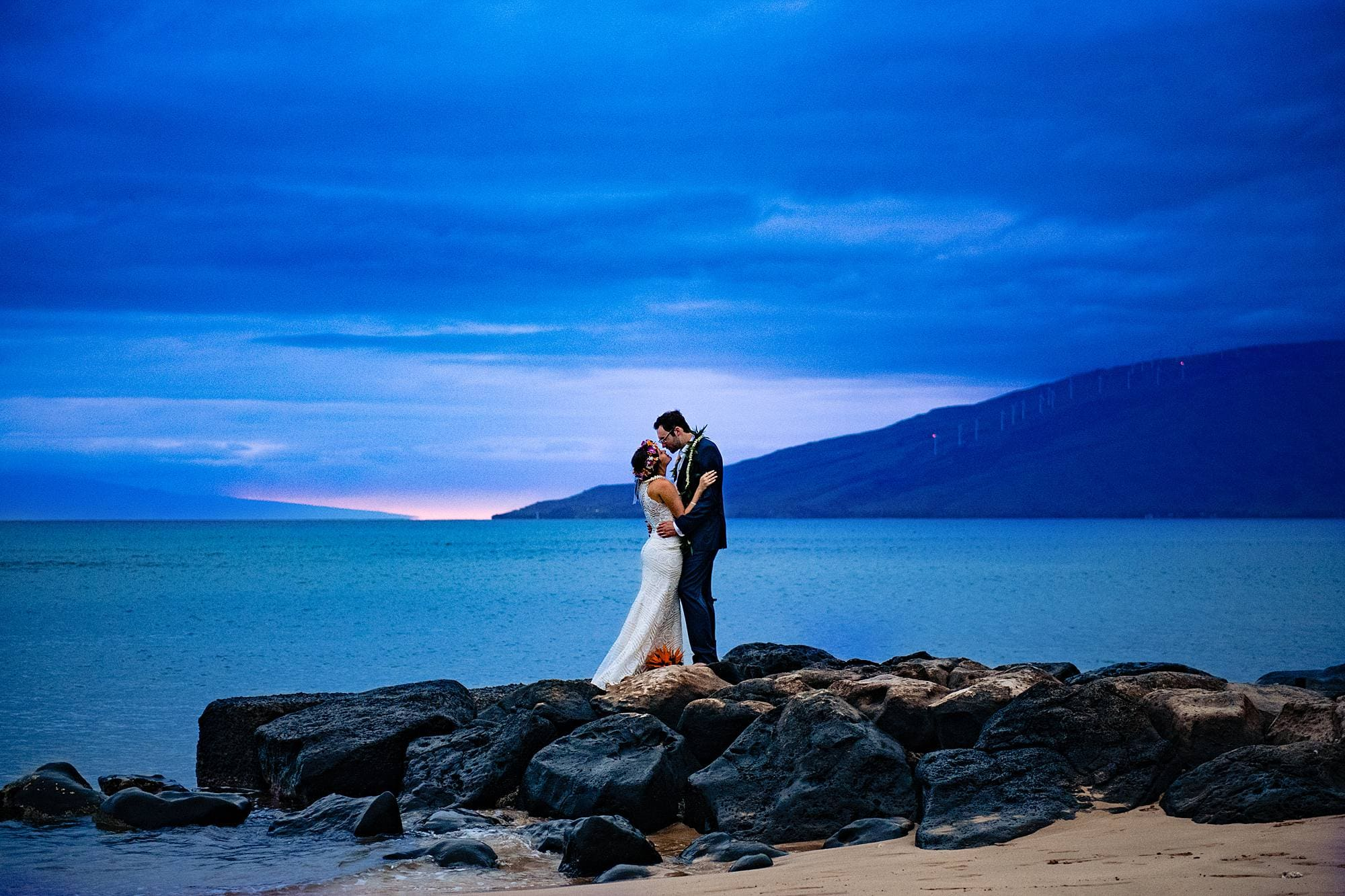 bride and groom kissing on rocks