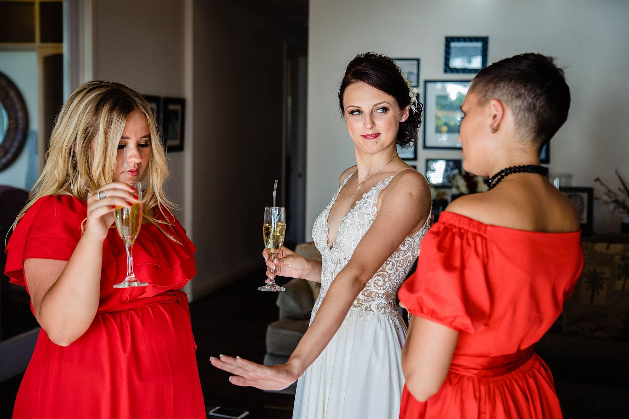 bride admiring wedding ring with bridesmaids