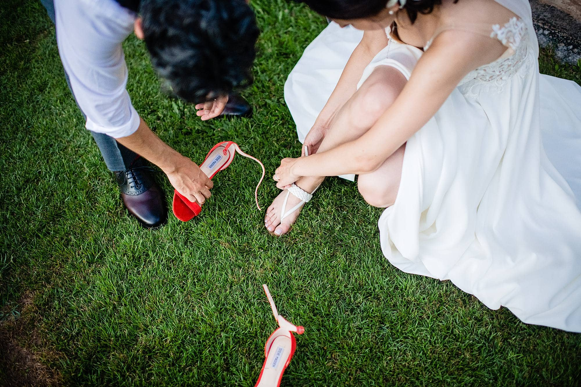 groom helping bride change into shoes