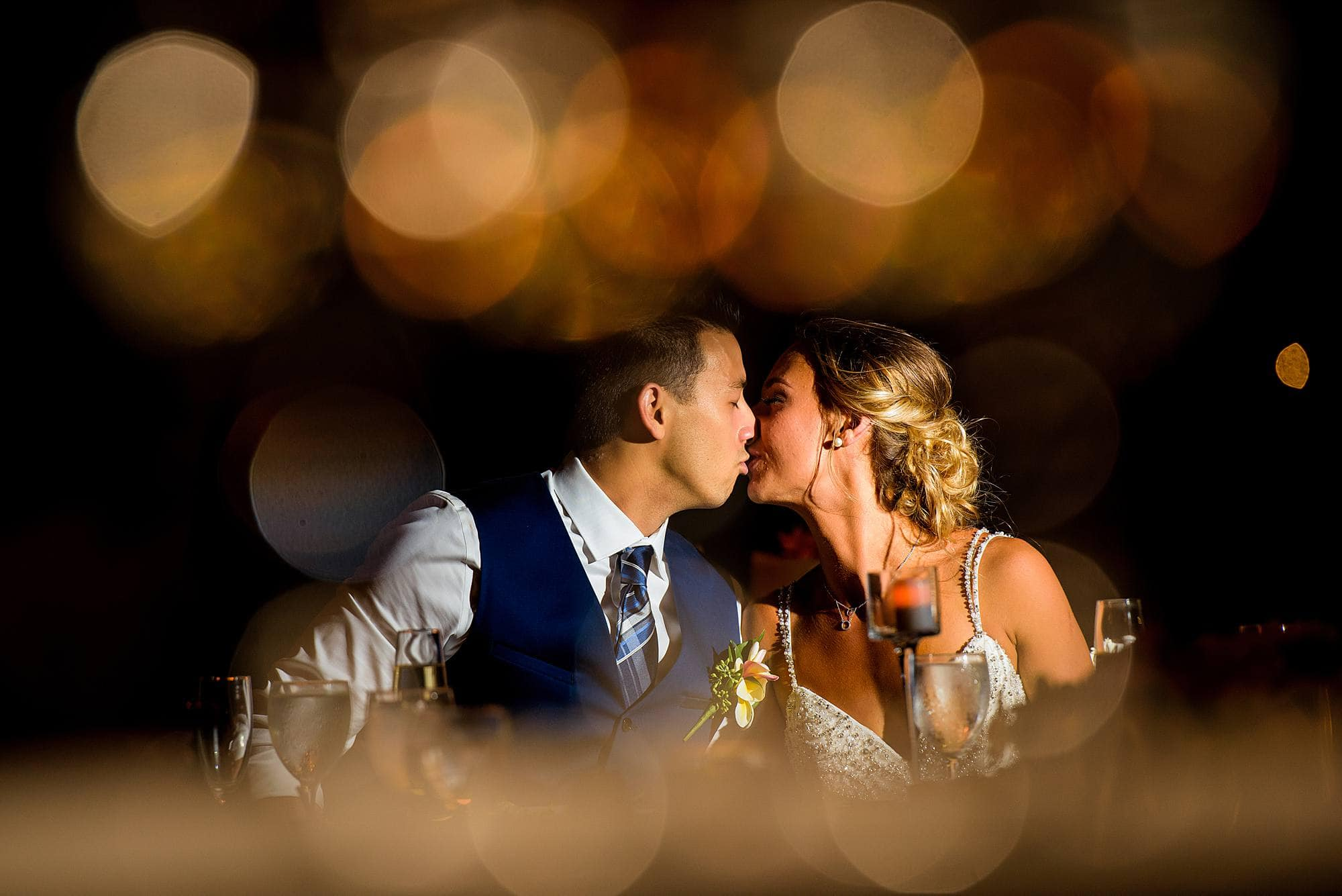 bride and groom kissing during dinner