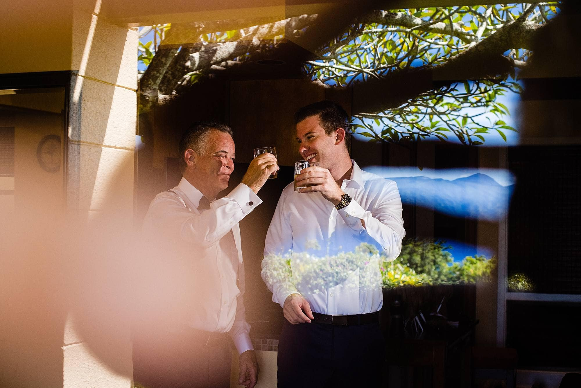 groom drinking whiskey with father before wedding