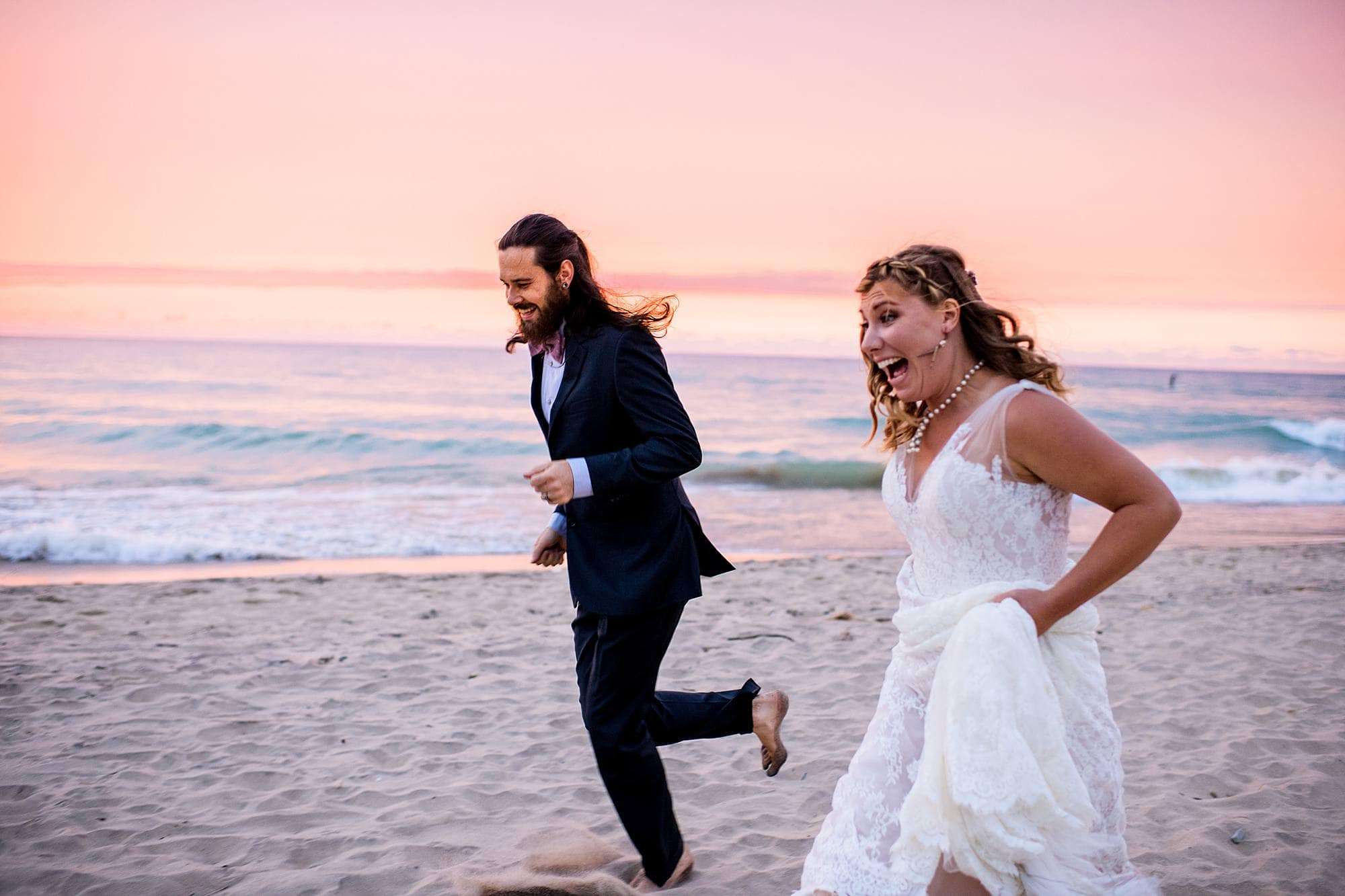 bride and groom running on the beach at lake michigan