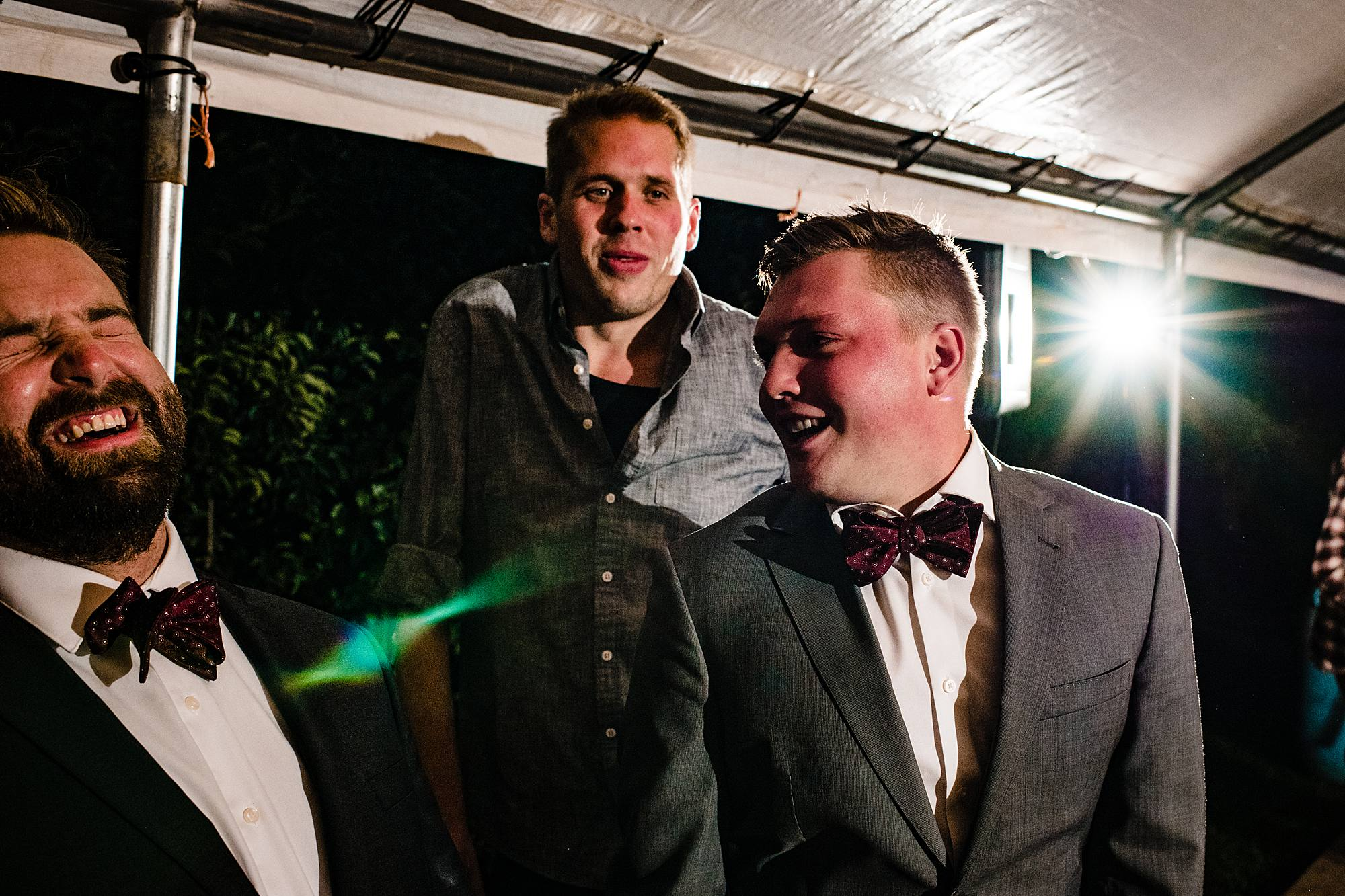 groomsment laugh at wedding reception at lemon creek winery