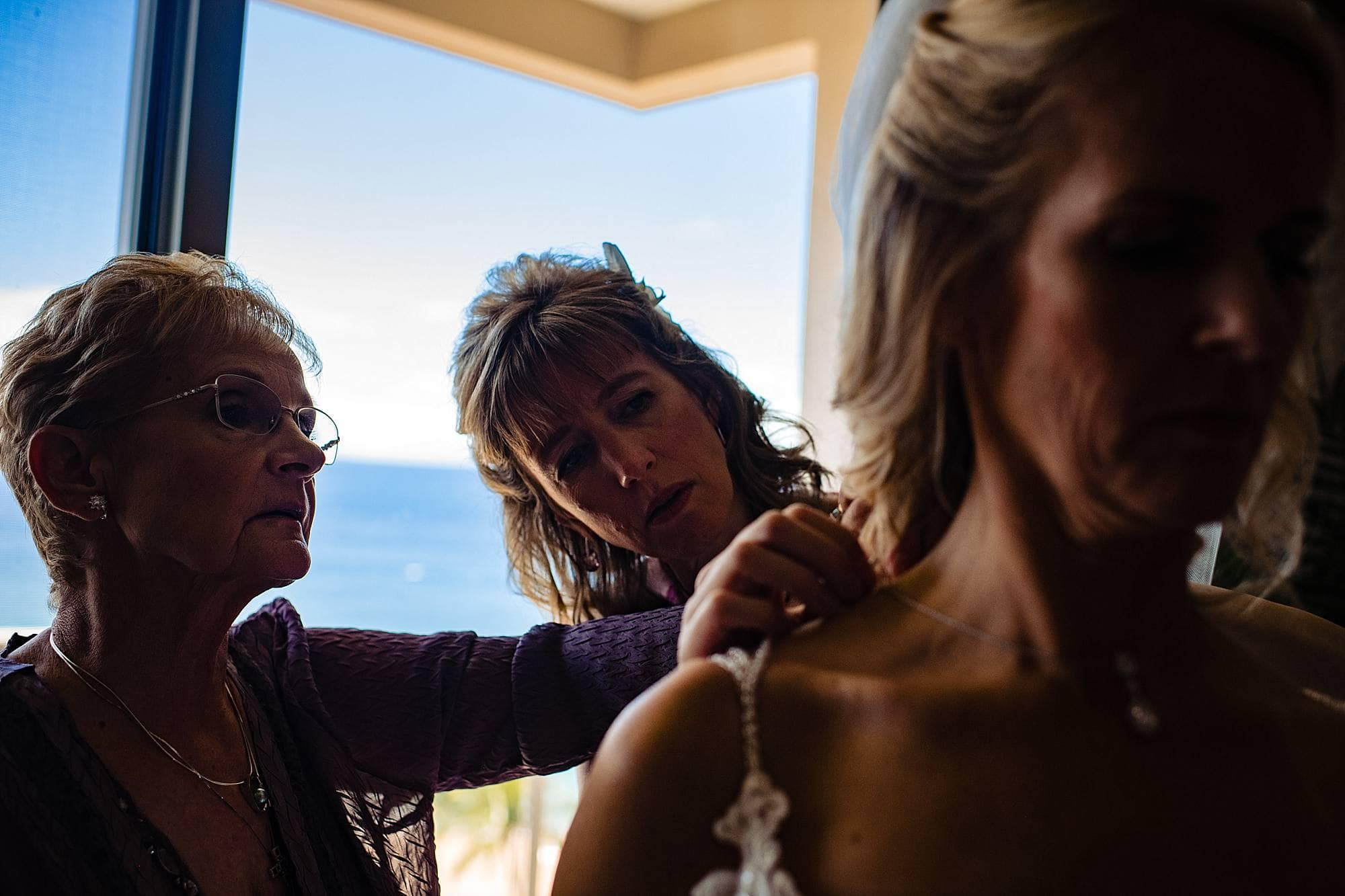 mother of the bride and maid of honor helping bride get ready